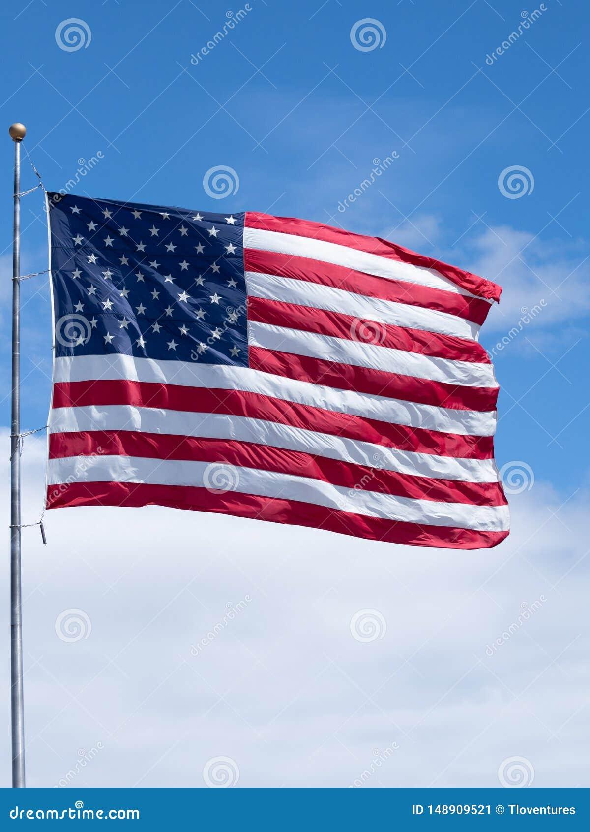 Pionowo flaga ameryka?ska na Chor?gwianym s?upie z niebieskim niebem i G?stymi Bia?ymi chmurami