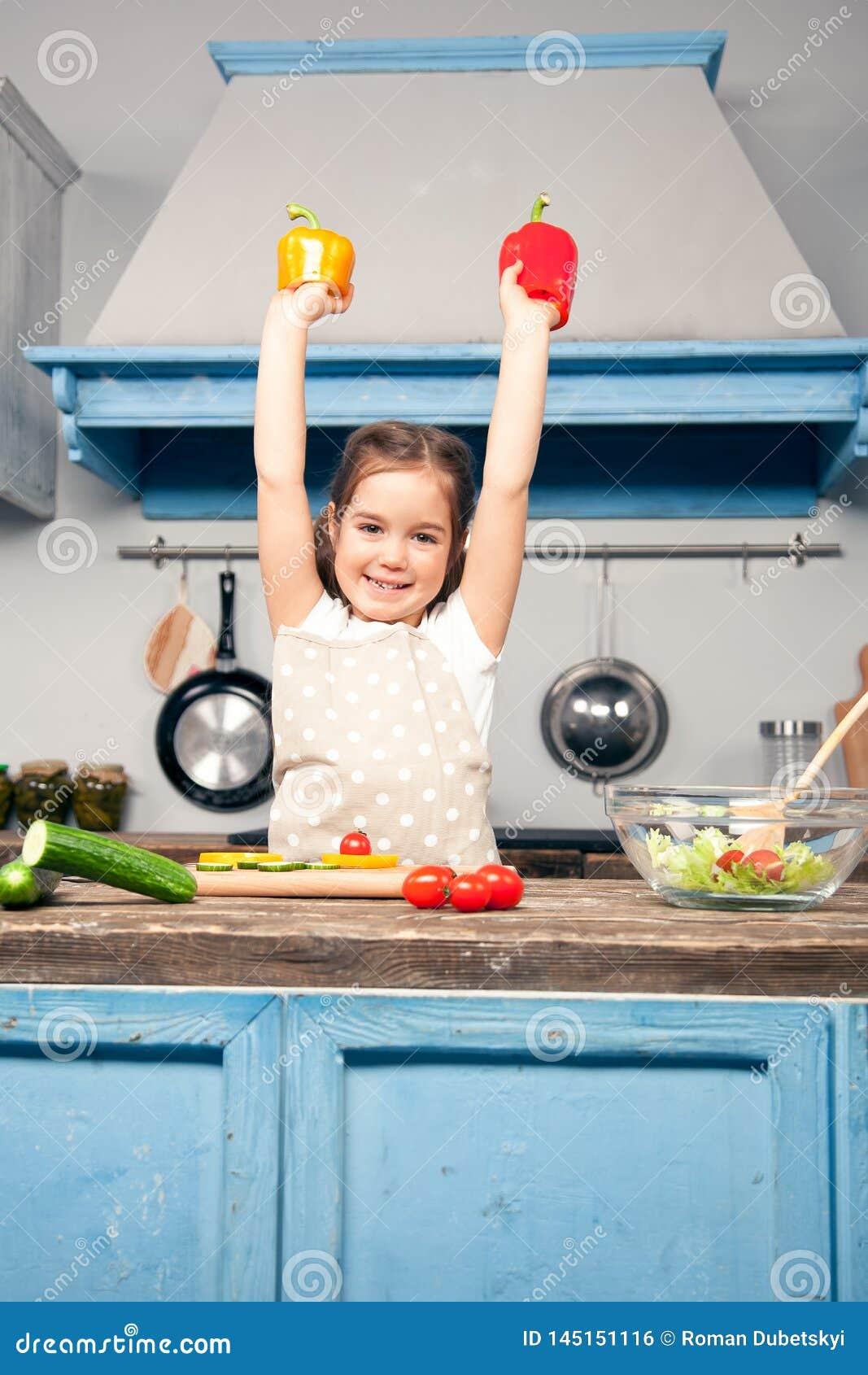 Pionowo fotografia piękna dziewczyna z ona ręki podnosić, w jej rękach trzyma Bułgarskiego pieprzu