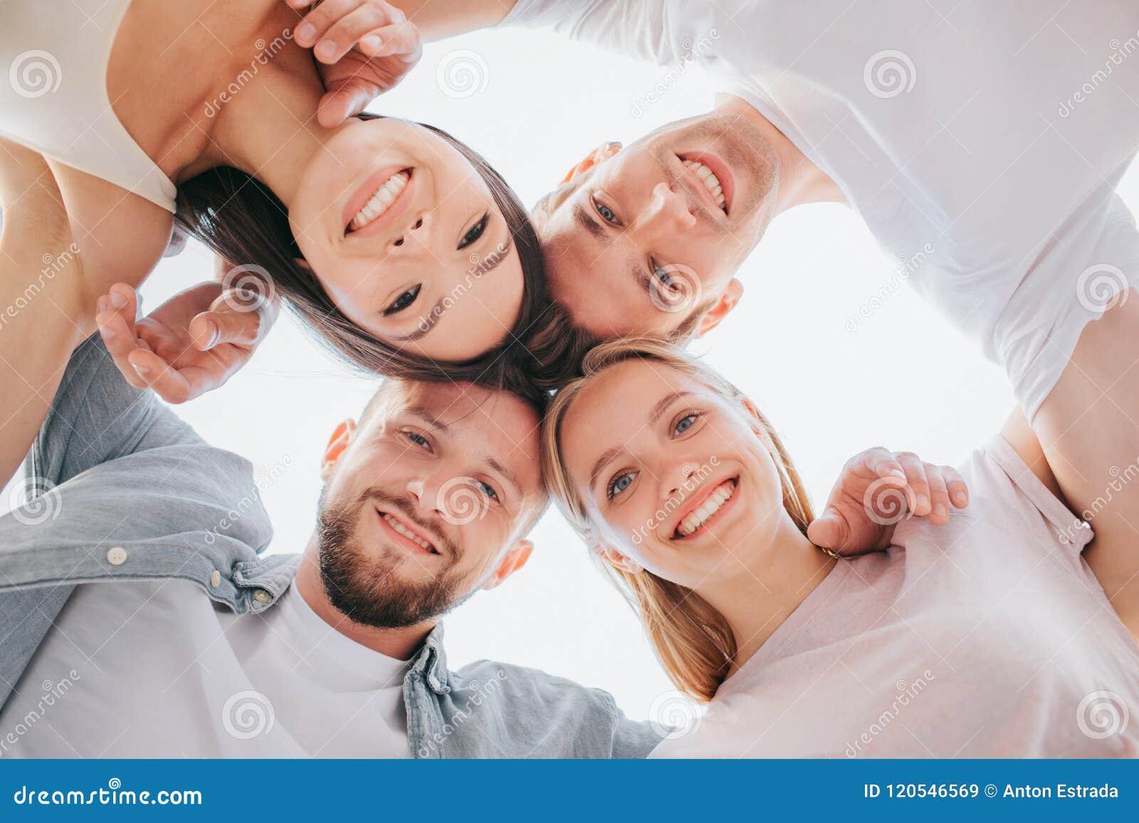 Pionowo obrazek młodzi człowiecy i kobiety szczęśliwi i pozytywni stoi blisko do each inny i patrzeje w dół na kamerze one