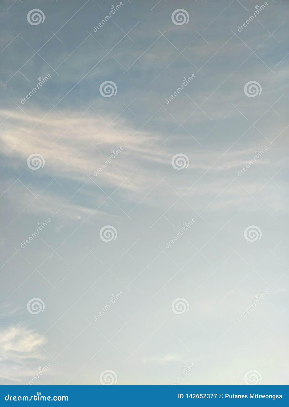 Pionowo wizerunek niebieskie niebo i biel chmurnieje na dniu