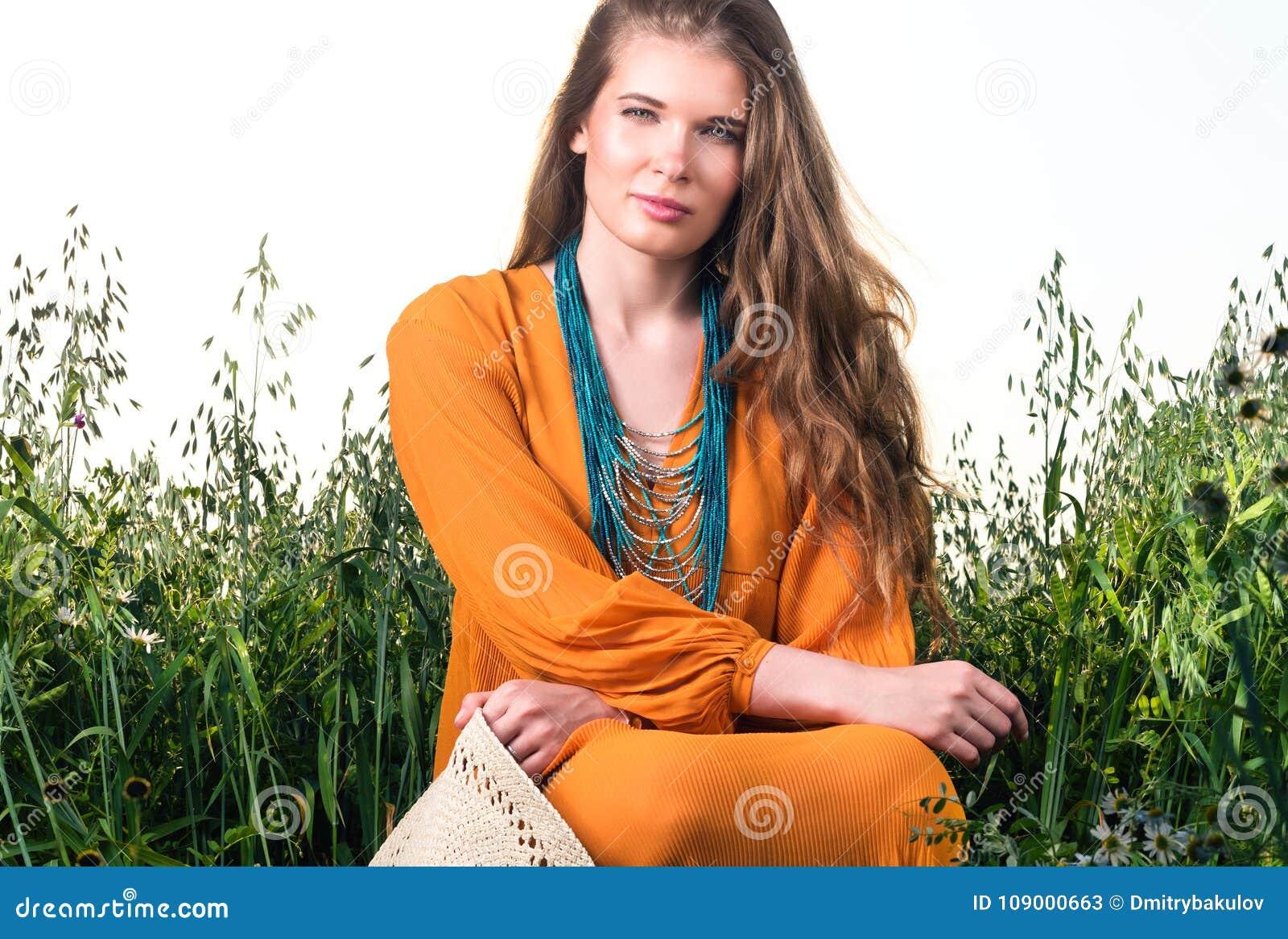 Pionowo zbliżenie portret młodej kobiety obsiadanie w wysokiej trawie