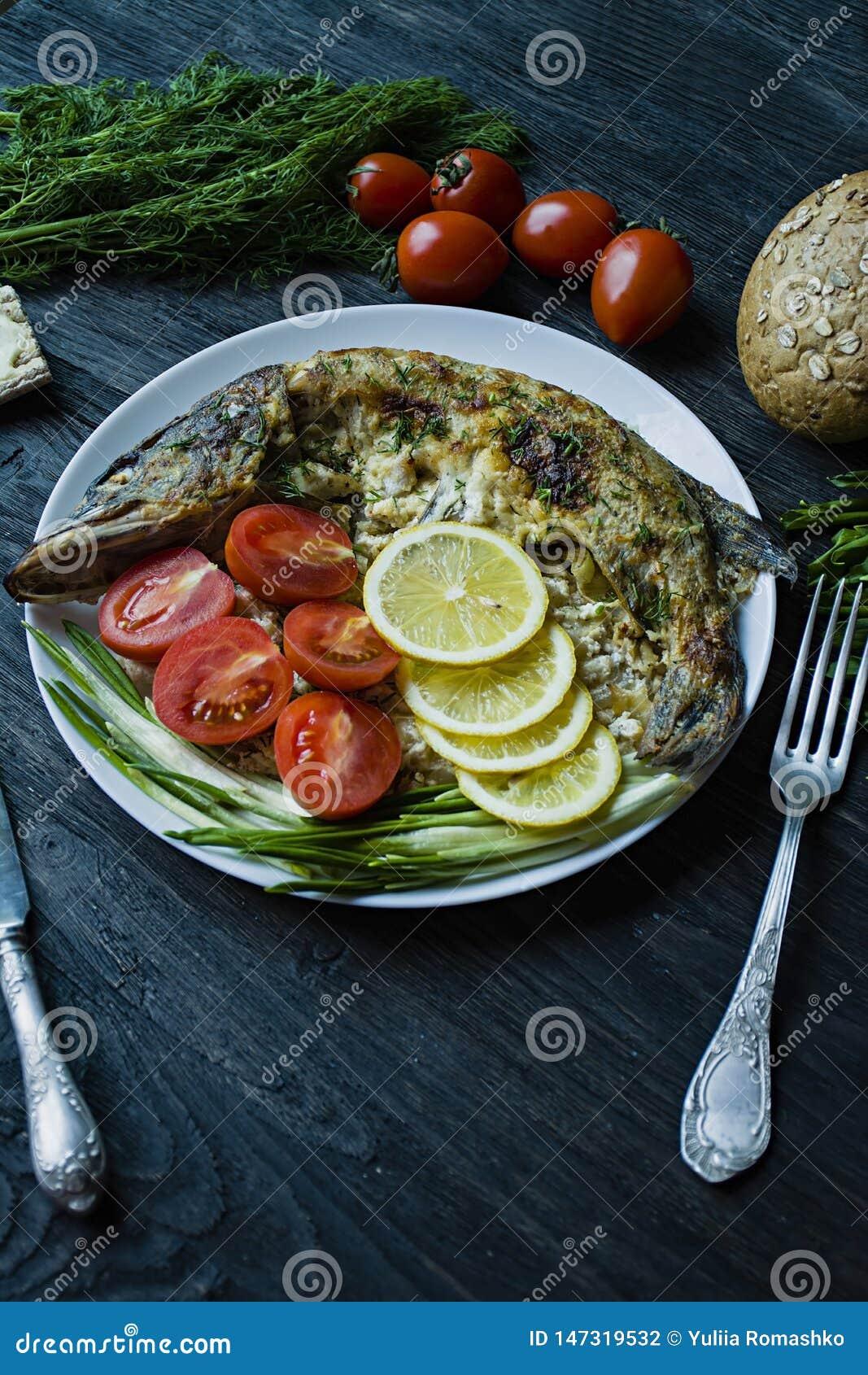 Pique cozido no forno, decorado com vegetais e ervas Servir em uma placa Nutri??o apropriada Fundo de madeira escuro