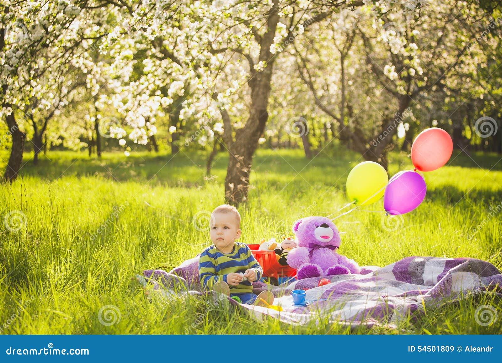 Pique-nique de famille enfant s asseyant parmi des jouets