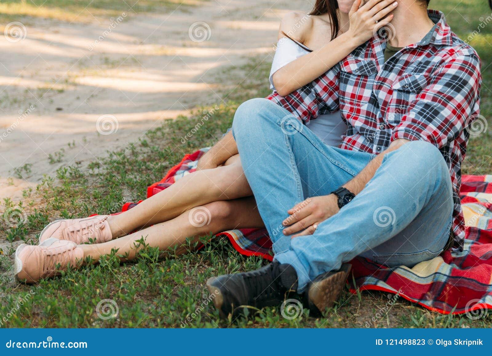 Pique-nique un type et une fille s asseyent sur un voile de plaid sur l herbe, étreindre et embrasser un homme dans une chemise e