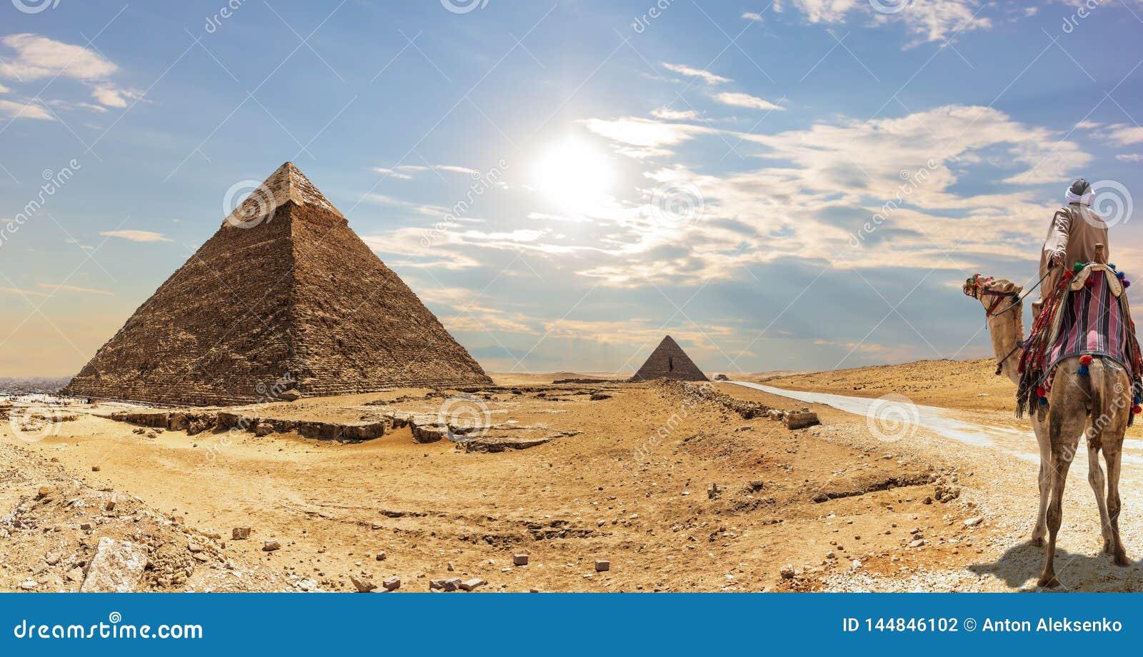 A pirâmide de Khafre e um beduíno em um camelo, Giza, Egito