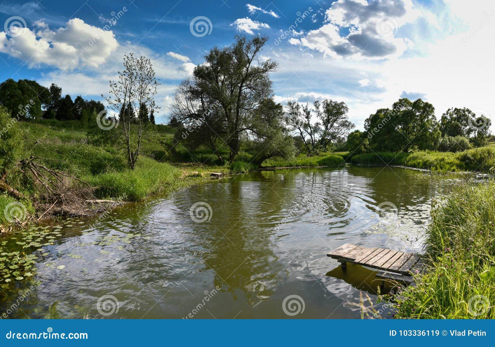 Pir på en lugna flod i sommaren Träpirbro i morgonen Ställe för att fiska i floden
