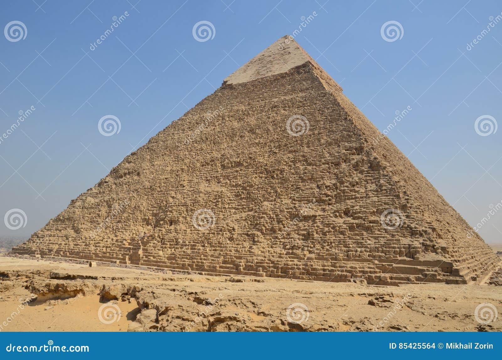 Piramide in polvere della sabbia sotto le nuvole grige