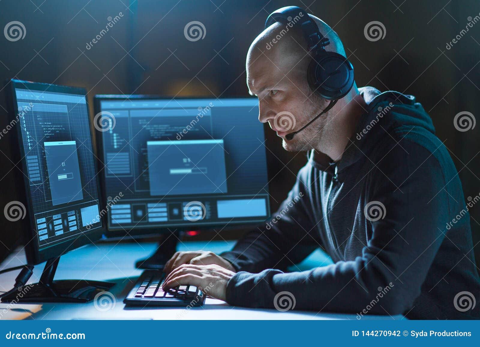 Pirata informático con el ordenador y las auriculares en sitio oscuro