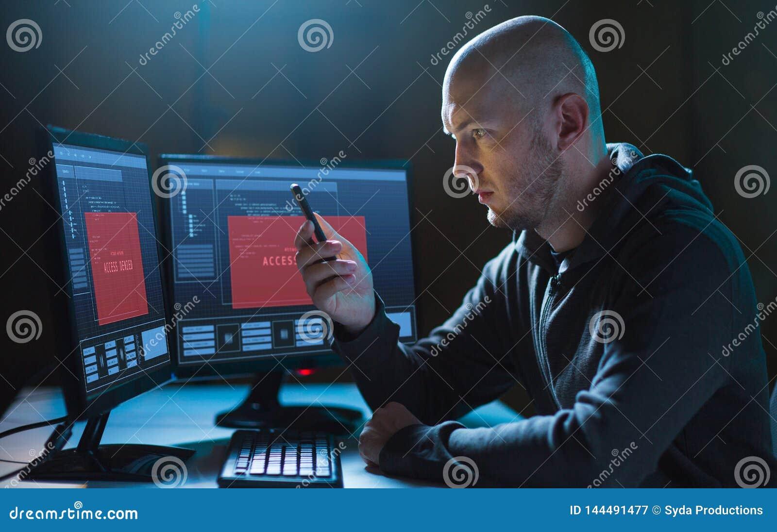 Pirata informático con smartphone y ordenadores en sitio oscuro