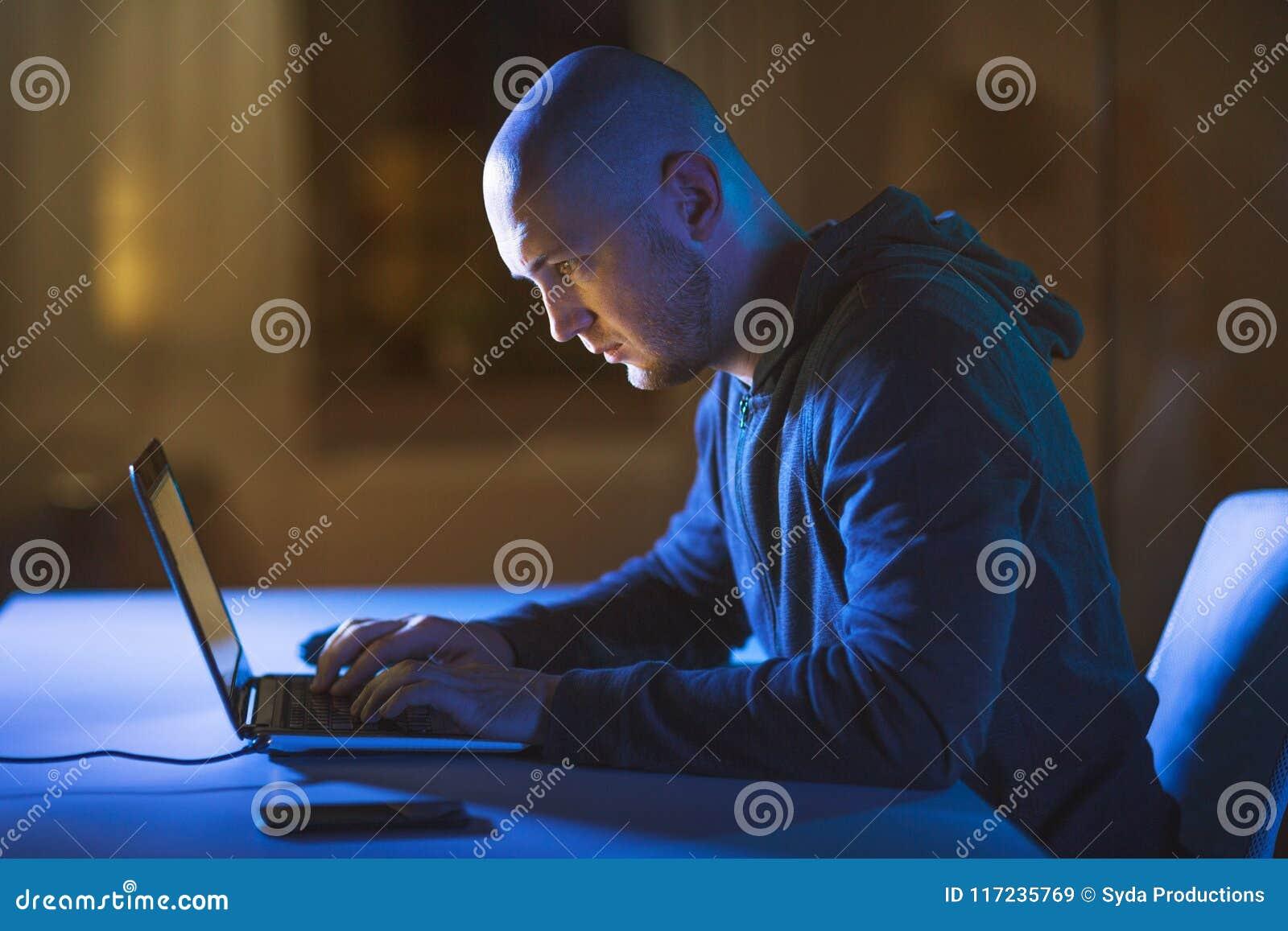 Pirata informático que usa el ordenador portátil para el ataque cibernético