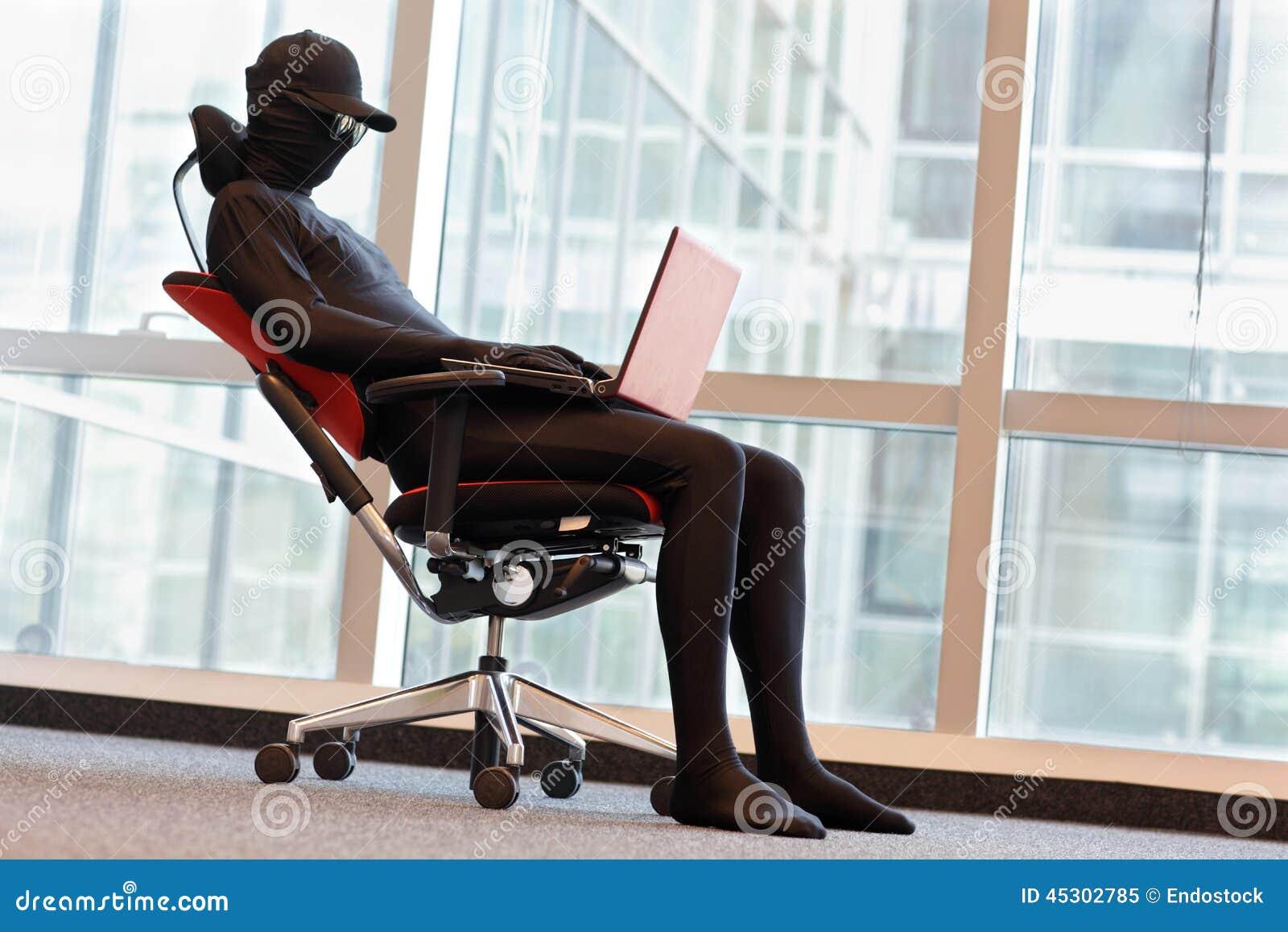 Pirate informatique anonyme travaillant avec l ordinateur portable dans le bureau