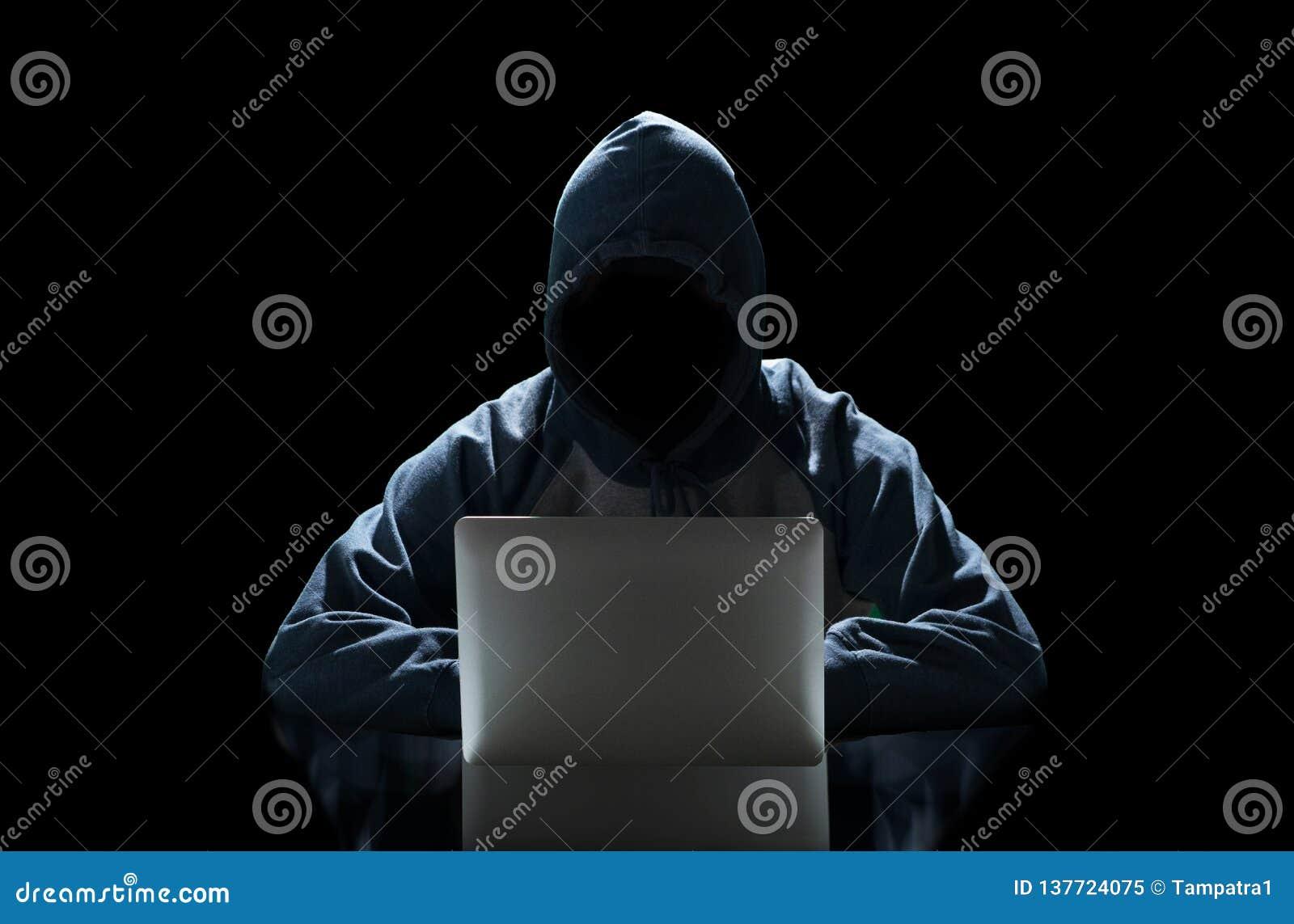 Pirate informatique dactylographiant sur un ordinateur portable d isolement sur le fond noir avec une matrice de fond de moniteur