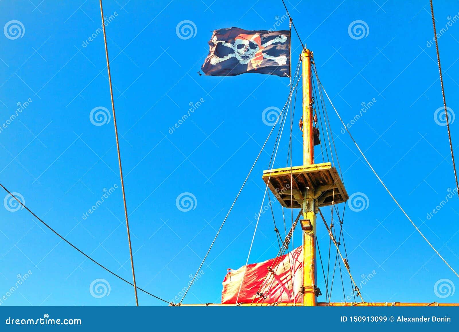 Piratkopiera flaggan som hissas mot blå himmel