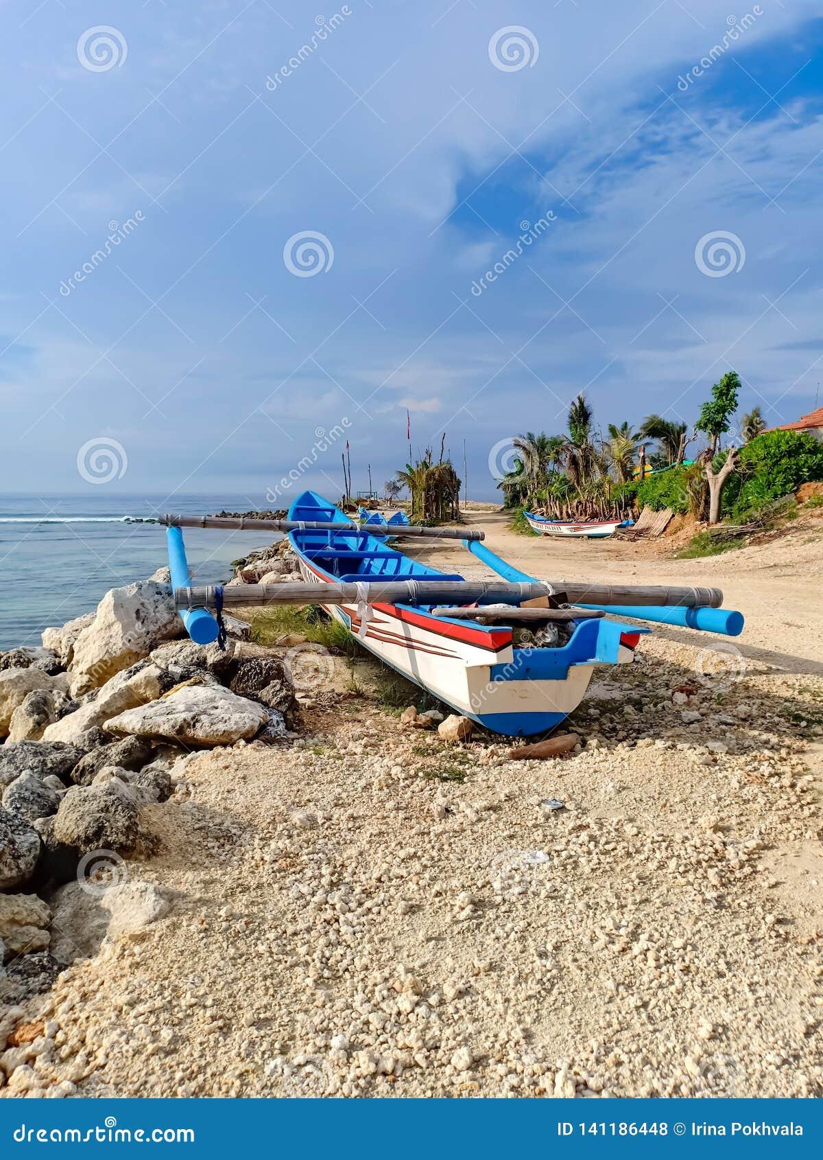 Piroga della barca del pescatore sulla riva dell Oceano Indiano DUA di Nusa, Bali, Indonesia