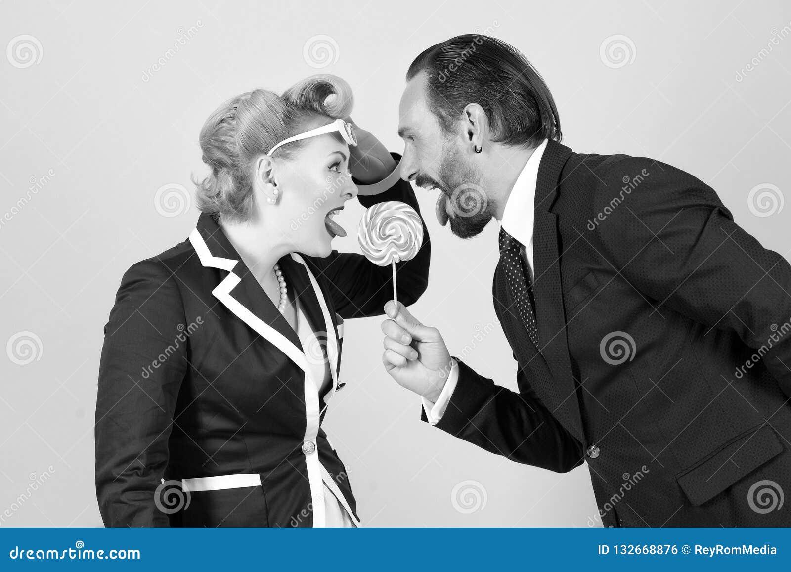 Pirulito no perigo dois gerentes que lutam por um doce no fundo cinzento