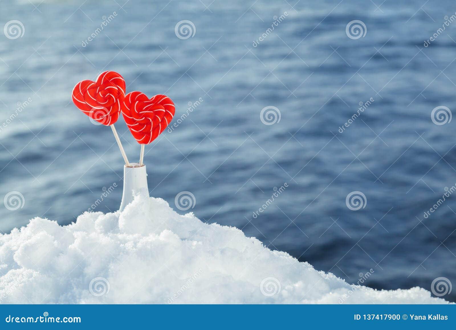 Pirulitos dos corações na neve no fundo de ondas do mar Data romântica, declaração do amor, o dia de Valentim