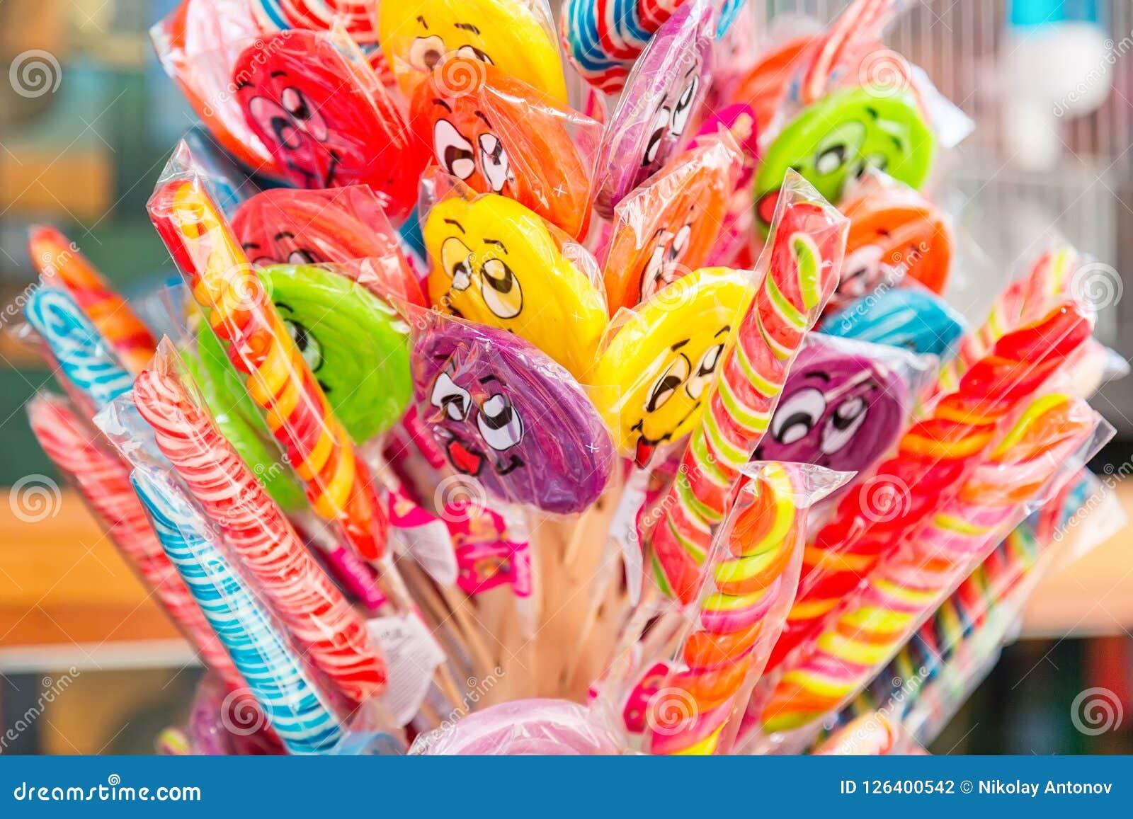 Pirulitos e doces coloridos com caras de sorriso fora para a venda