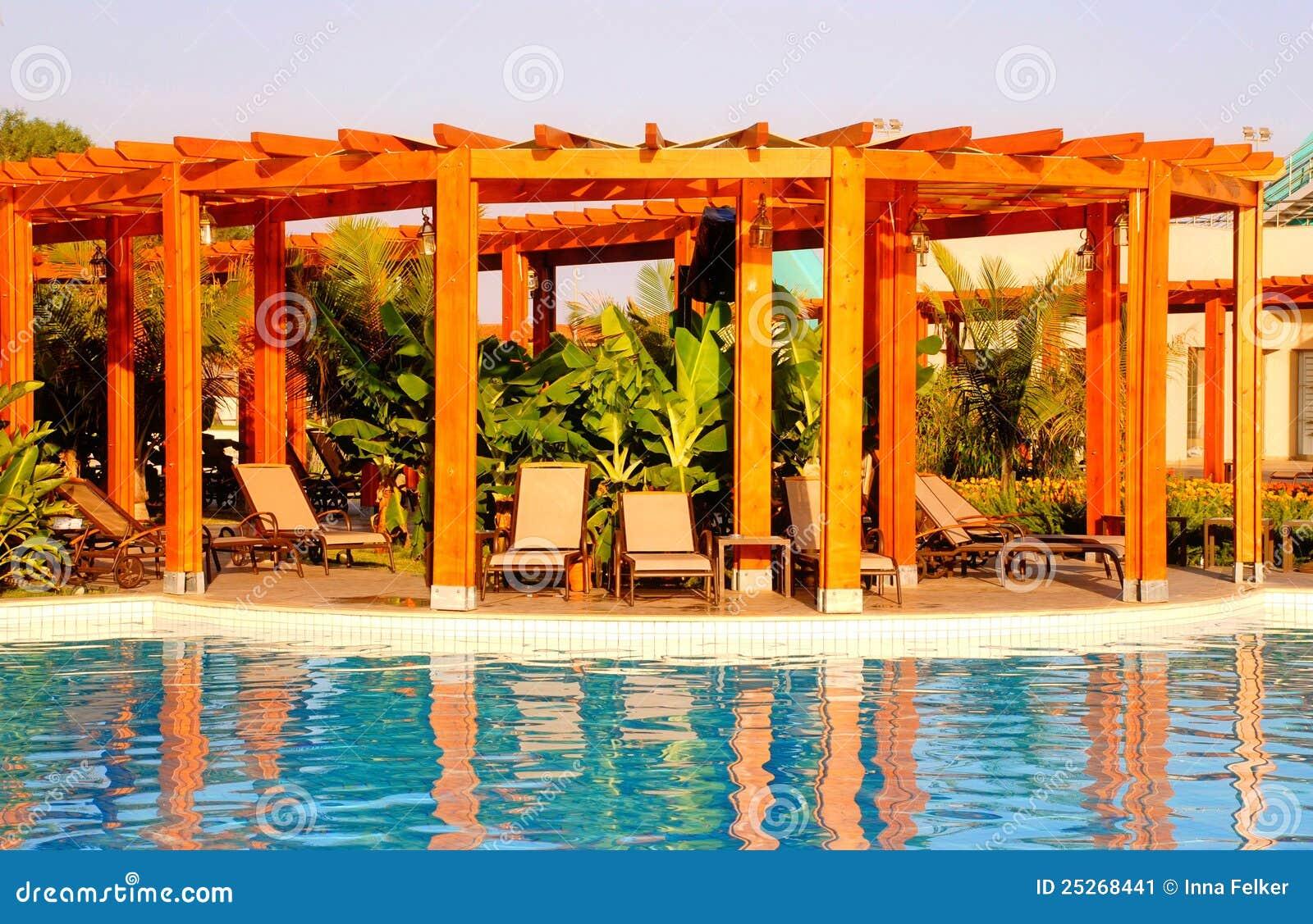 Imagem de Stock: Piscina do recurso pergola de madeira e cadeiras de  #C33608 1300x933