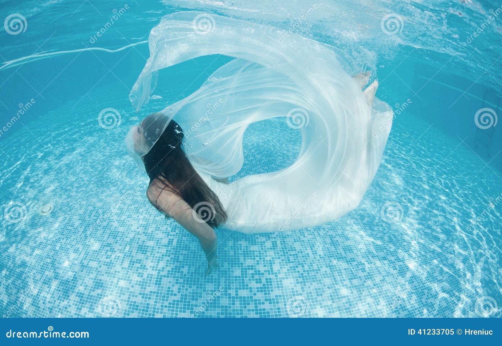 Piscine bleue de jour ensoleillé de beau de femme de fille de robe bain sous-marin blanc de plongée