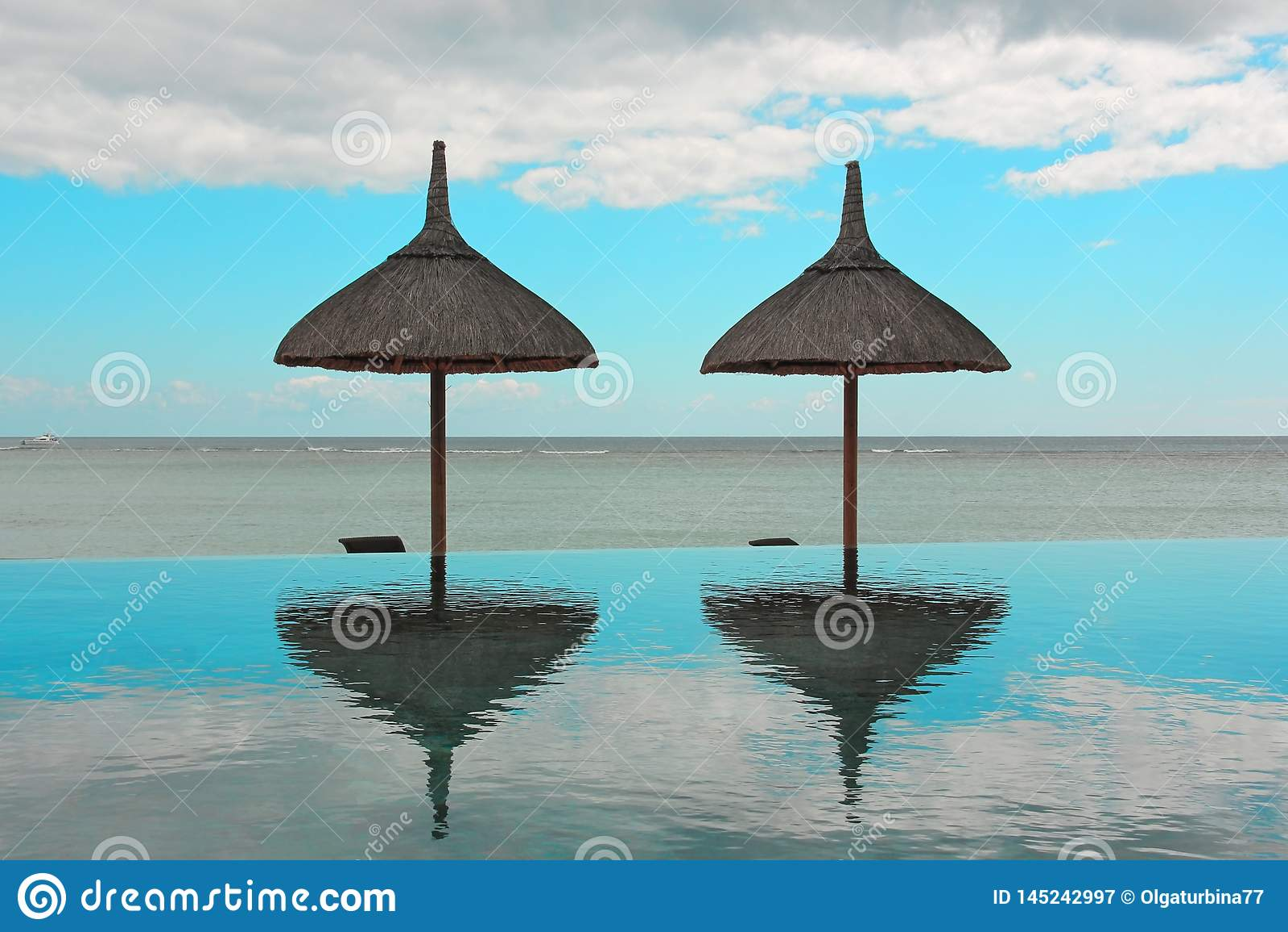 Piscine de parapluies de plage et d infini ? une station de vacances tropicale donnant sur l oc?an calme un jour d ?t