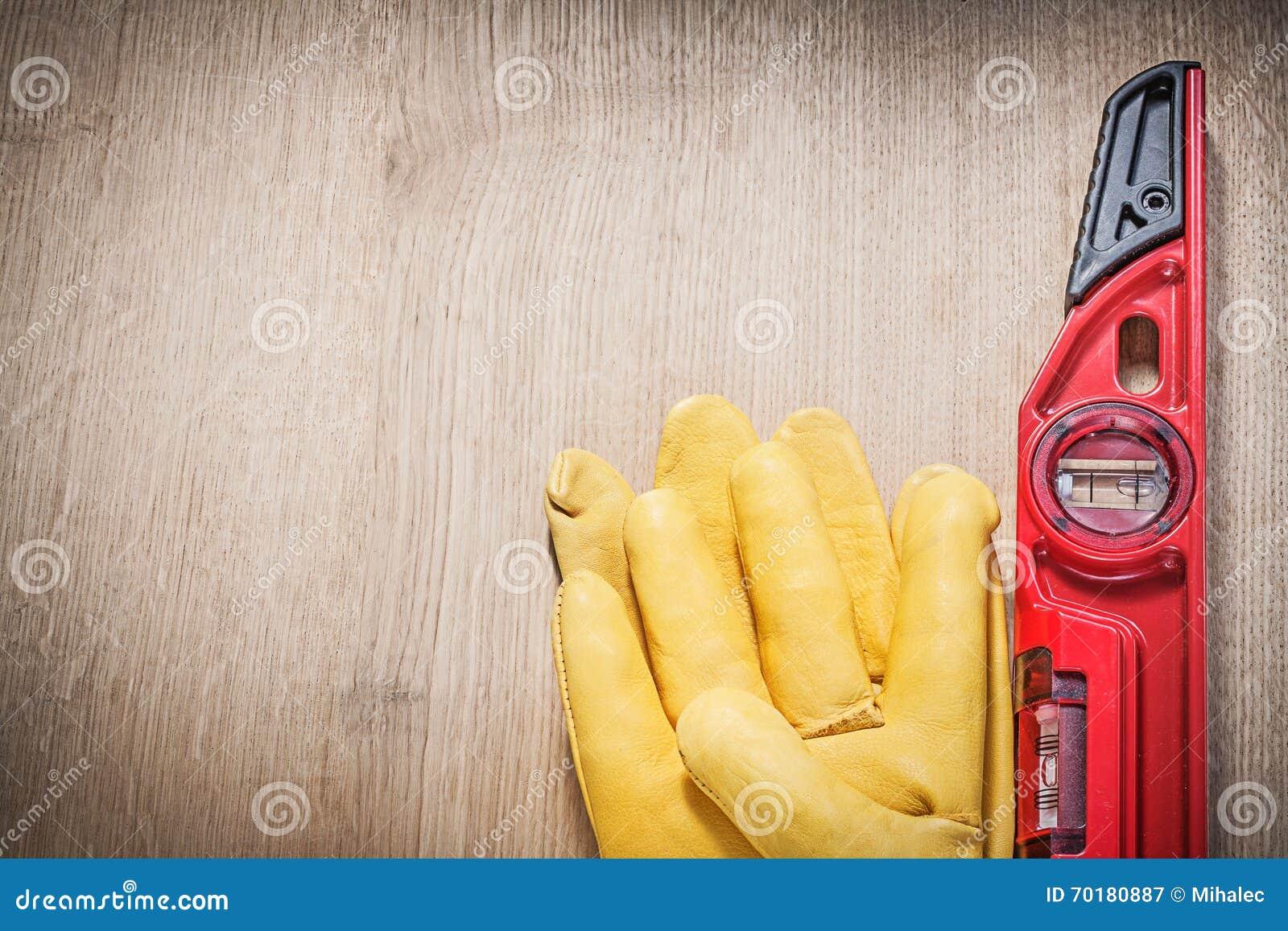 Piska den röda konstruktionsnivån för skyddande handskar på träbräde