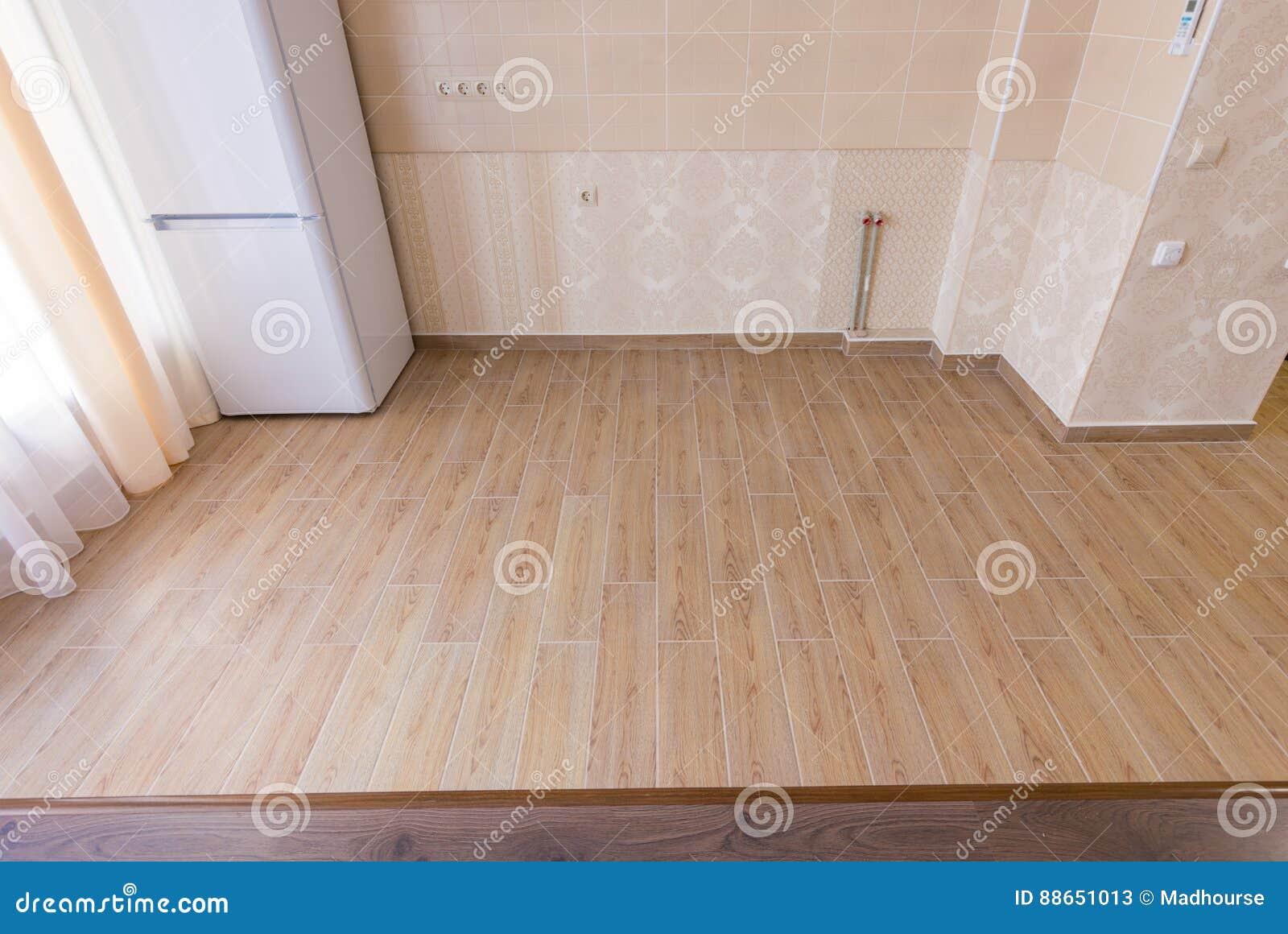 Piso de la división en las tejas interiores, de cerámica de la cocina confinadas con el suelo laminado en la sala de estar