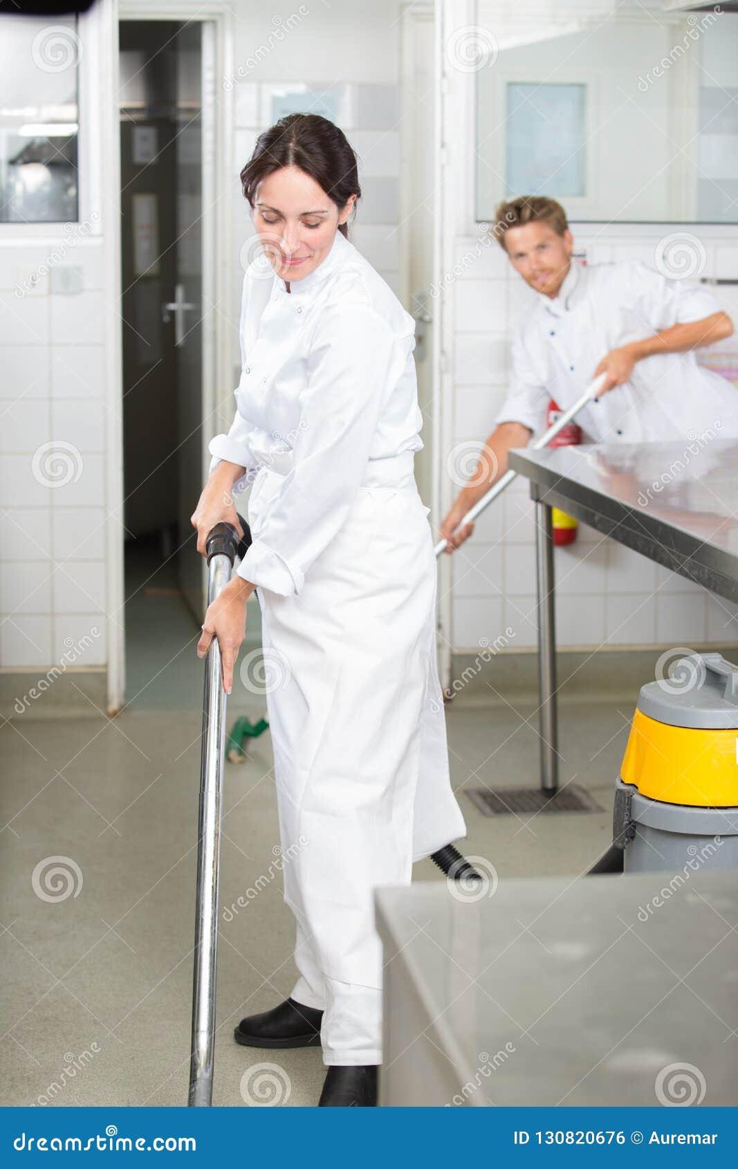 Piso de la limpieza del hombre y de la mujer en cocina del profesional