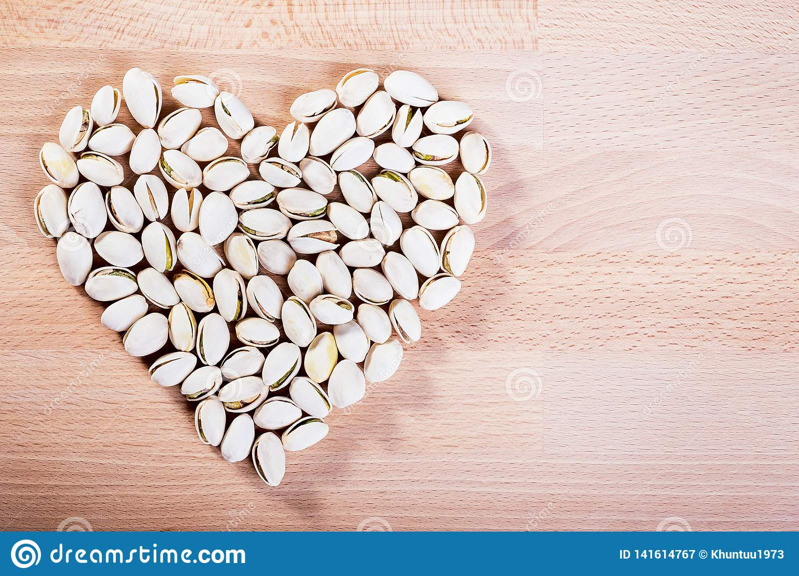 Pistachio nuts forming a heart-shape on wooden floor background