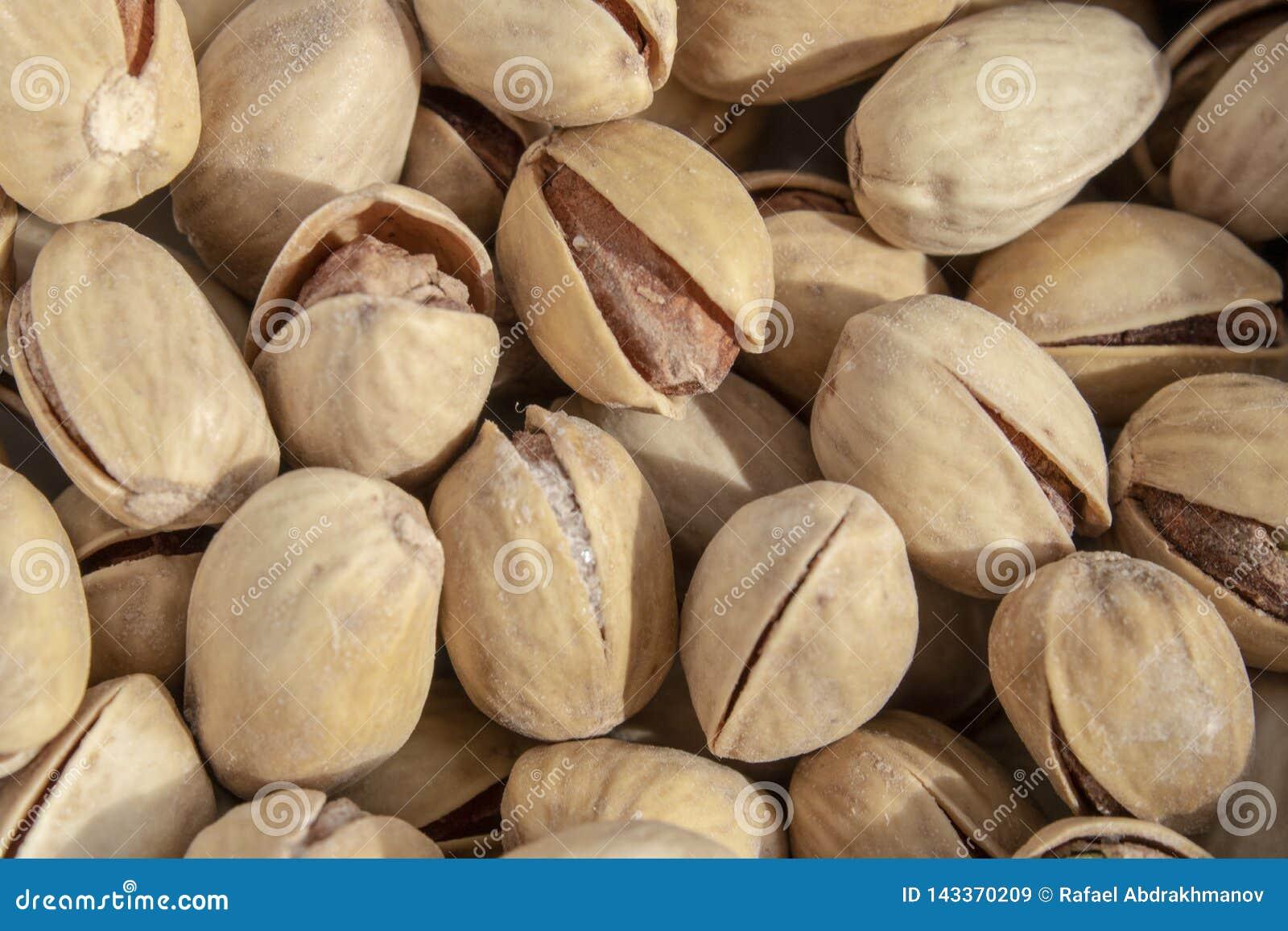 Pistachos abiertos deliciosos salados en un cuenco fondo natural marrón de nueces naturales