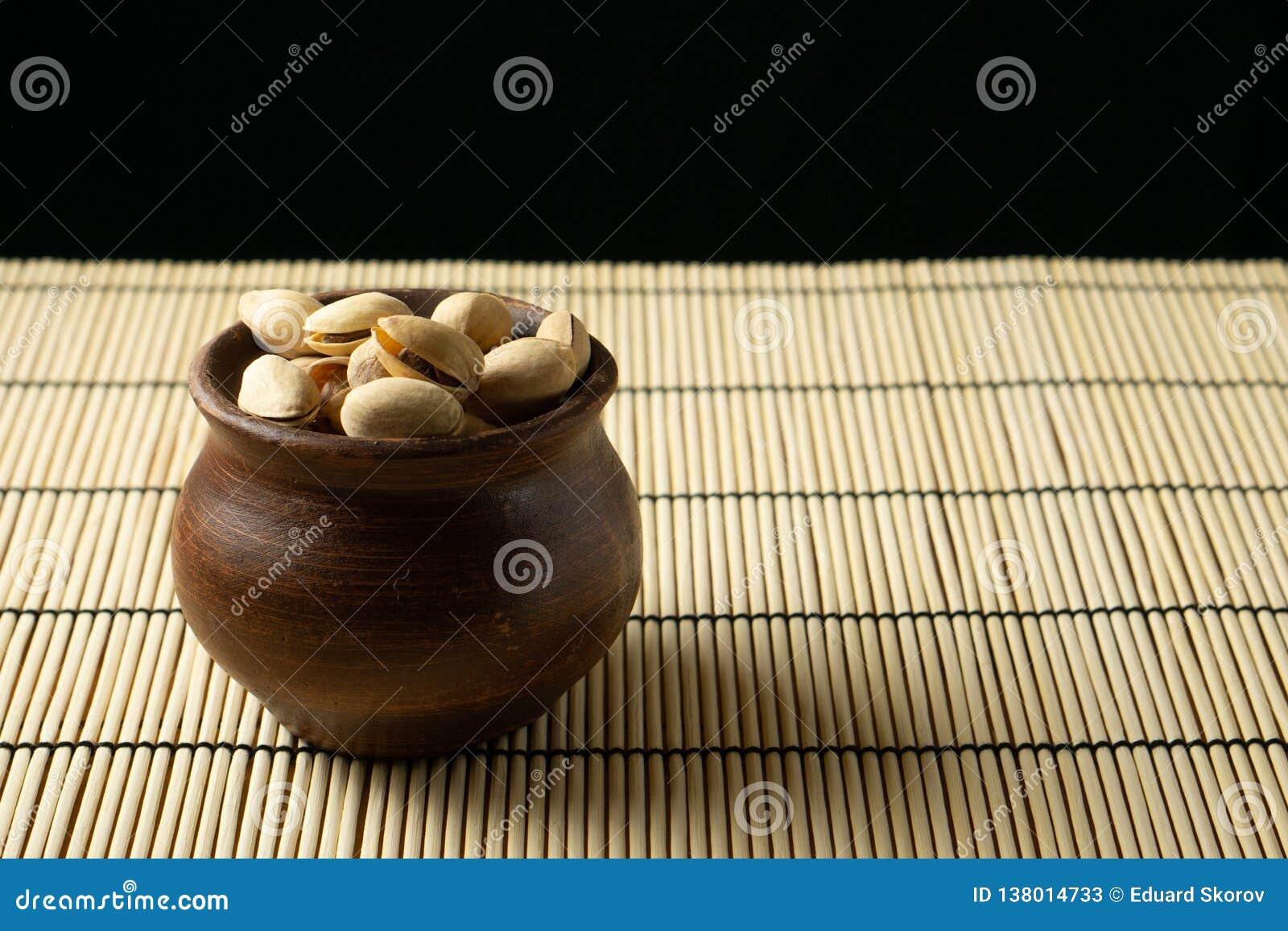 Pistacje w glinianym pucharze na stole