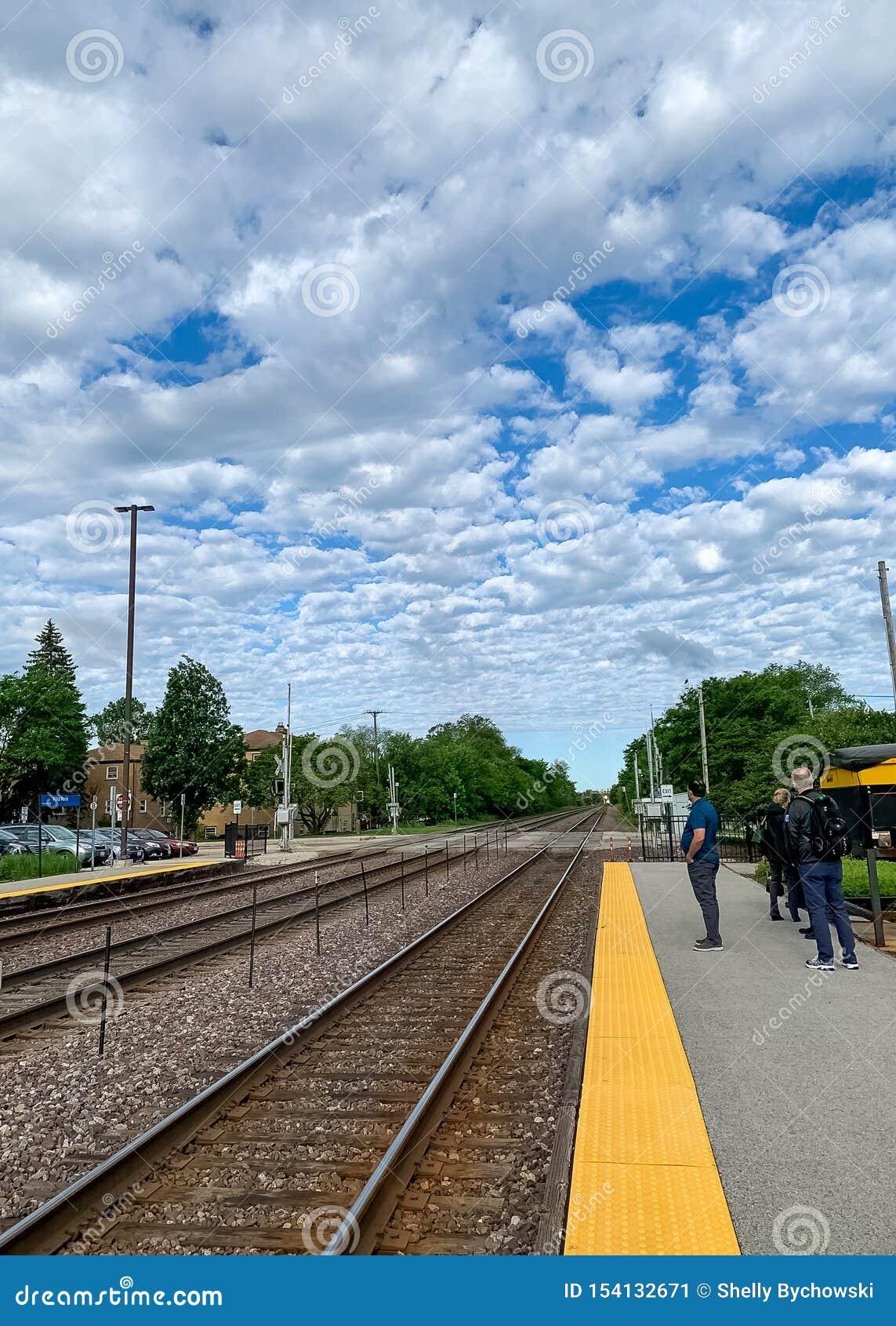 Pistas de ferrocarril que desaparecen el punto en un cielo nube-llenado estrato