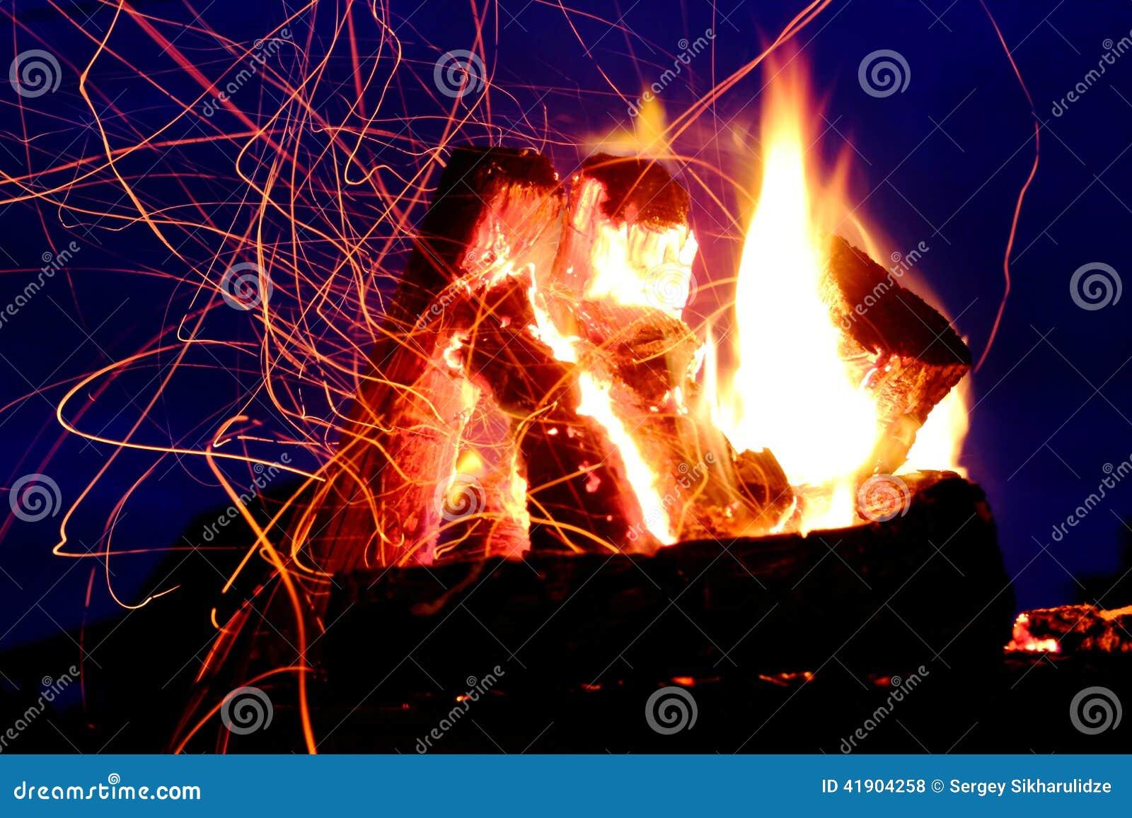 Pistas de la llama y de las chispas sobre el cielo azul marino