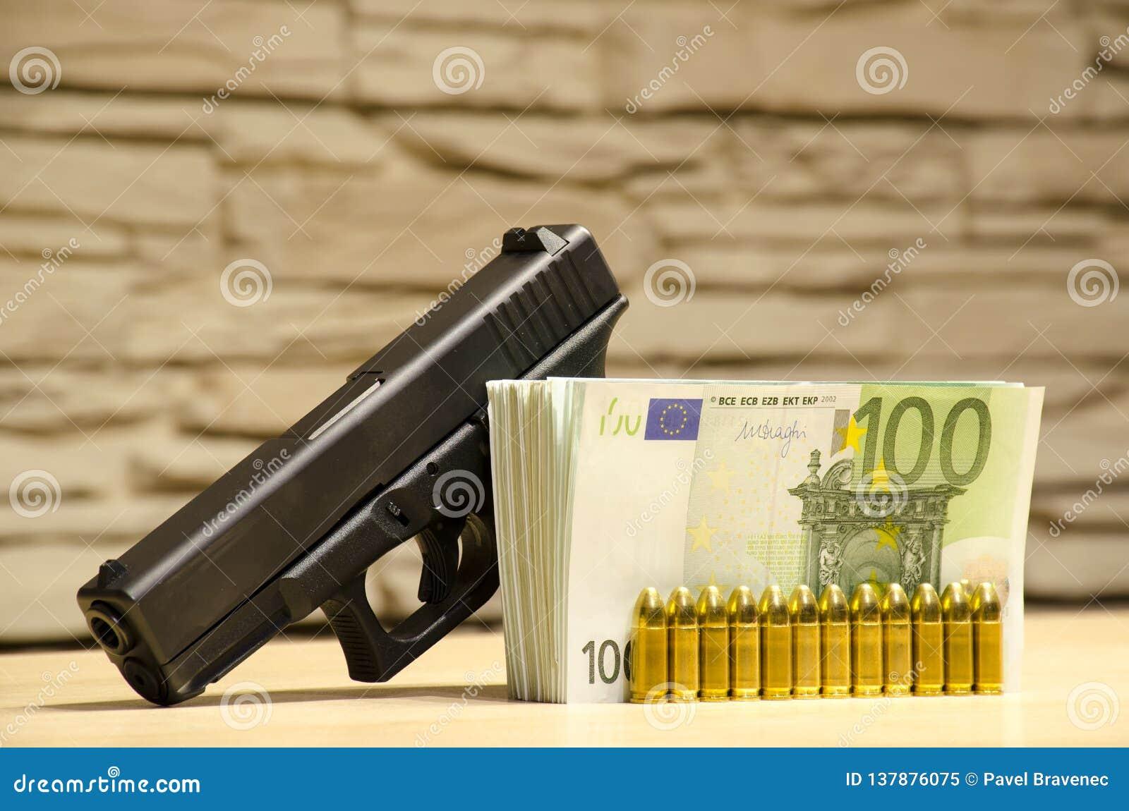 A pistola com balas fica atrás do dinheiro com retrocesso bllured da parede