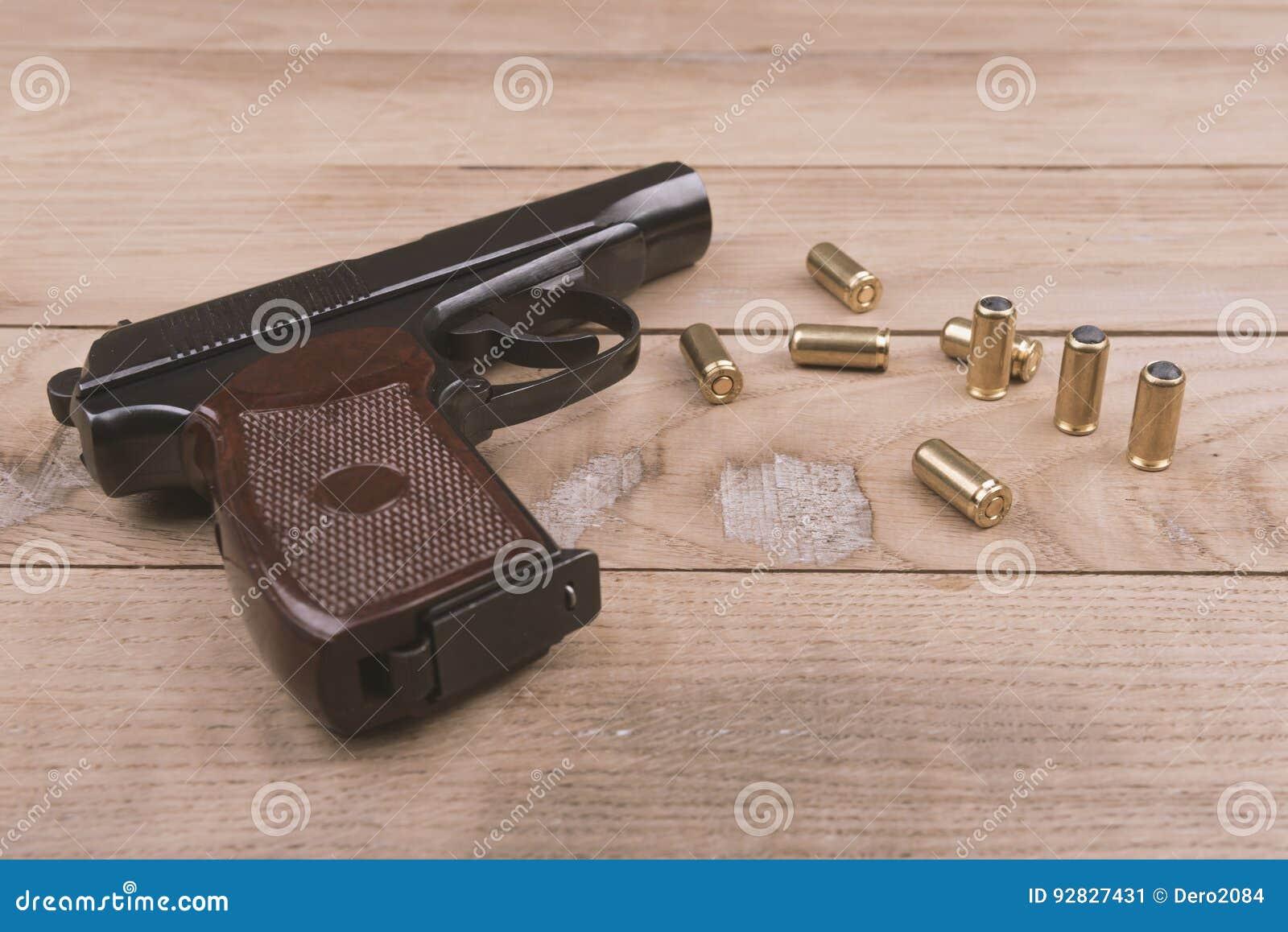 Pistolet traumatique avec les balles et la cartouche sur la surface en bois, ensemble