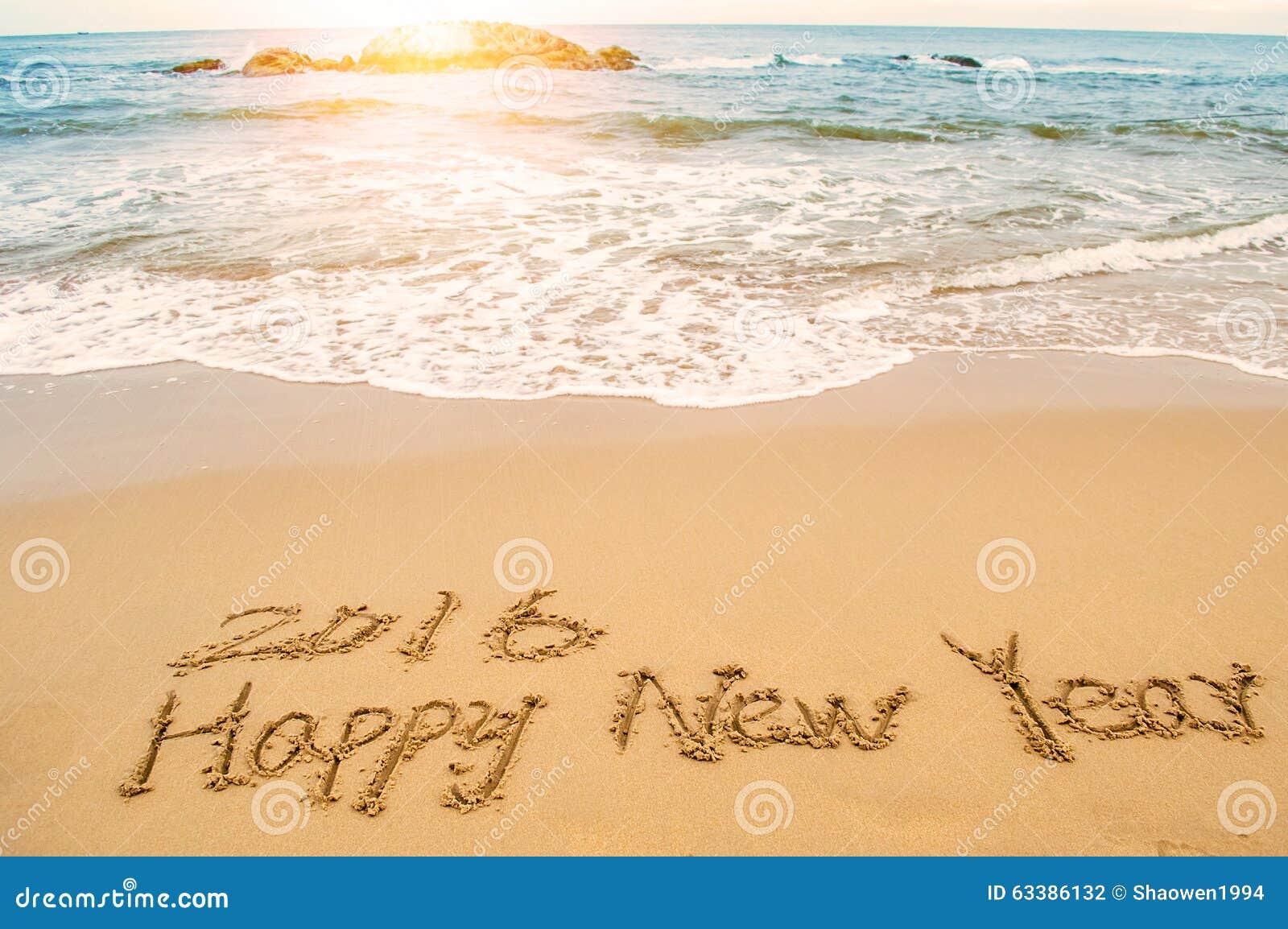 Pisze szczęśliwego nowego roku 2016 na plaży