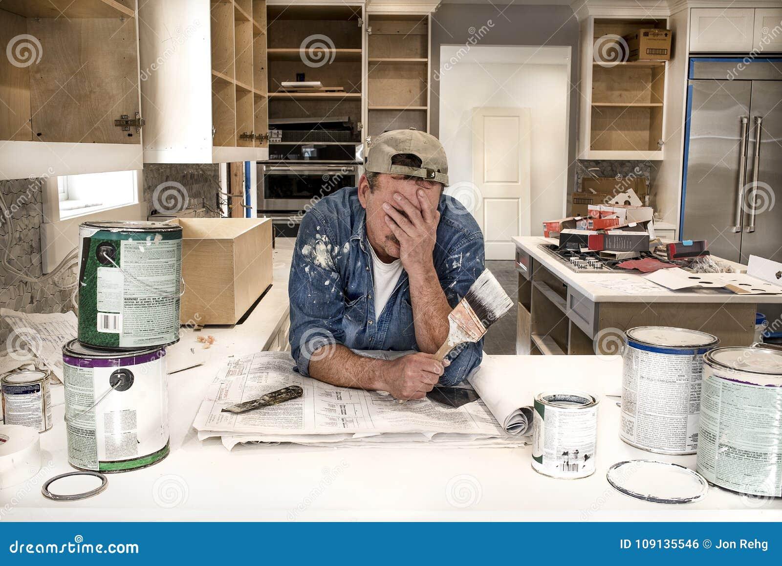 Pittore esaurito e stanco con il fronte in mani che tengono il pennello bagnato in cucina domestica sudicia con le latte della pi