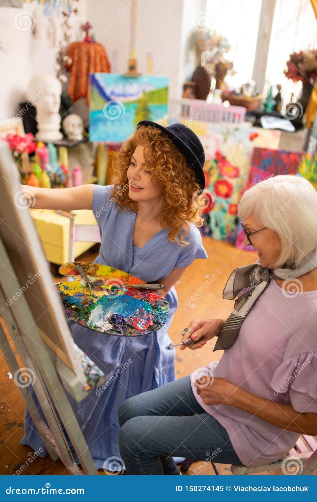 Pittura d uso del vestito e del cappello dal giovane artista vicino all insegnante