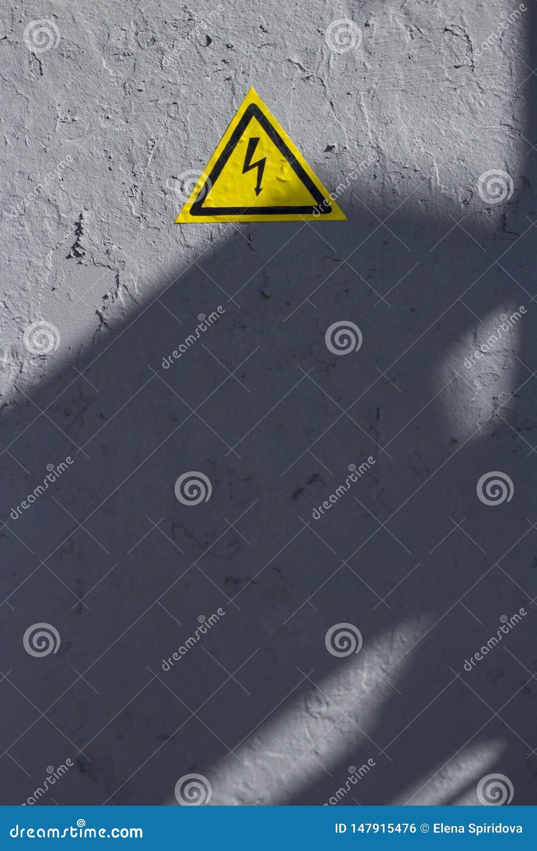 Pittura grigia incrinata con la percezione dell icona gialla del triangolo