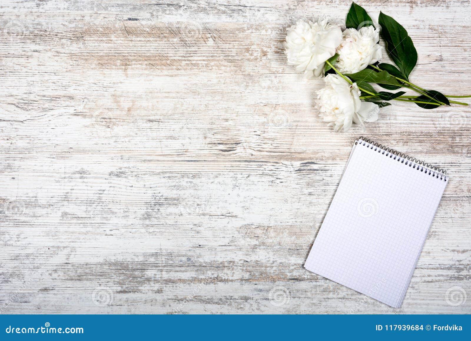 Pivoine blanche et bloc-notes pour des entrées dans une cage, se trouvant sur une vieille table légère, mocap, vue plate, romane,