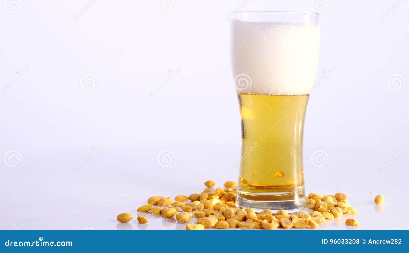 Piwo nalewa w szkło na białym tle z Kiszonymi arachidami