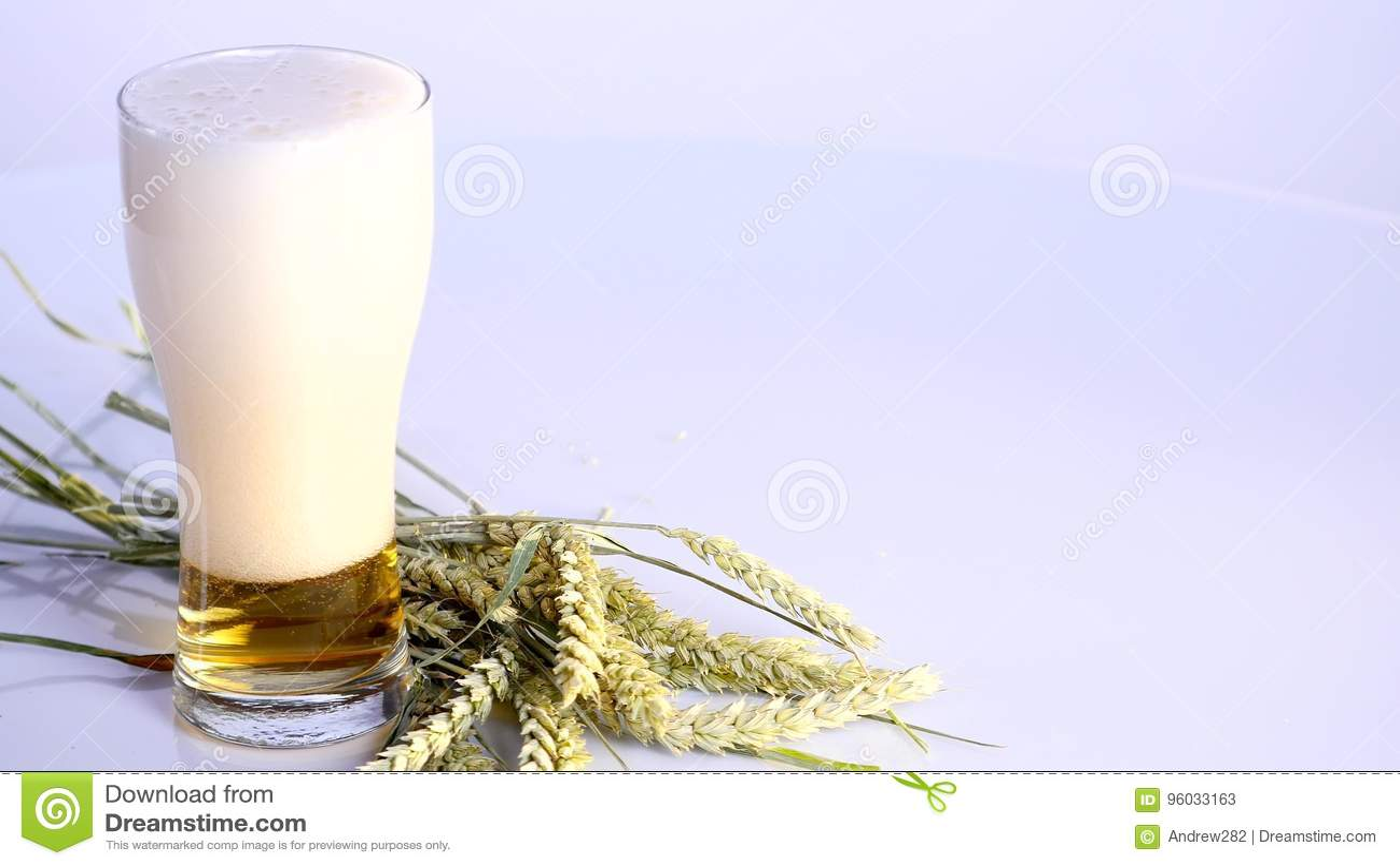 Piwo nalewa w szkło na białym tle z A wiązką banatka