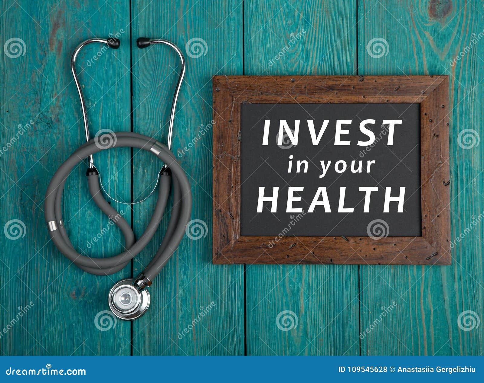 Pizarra con el texto y x22; Invierta en su health& x22; y estetoscopio en fondo de madera azul