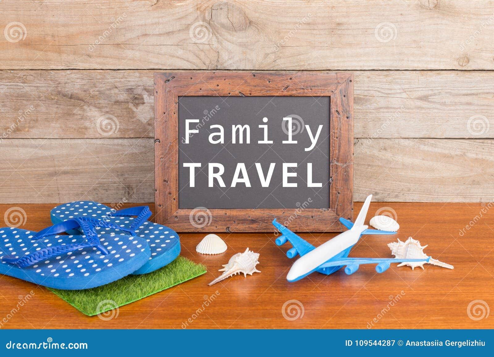 Pizarra con el texto y x22; Travel& x22 de la familia; , avión, chancletas, conchas marinas en fondo de madera marrón