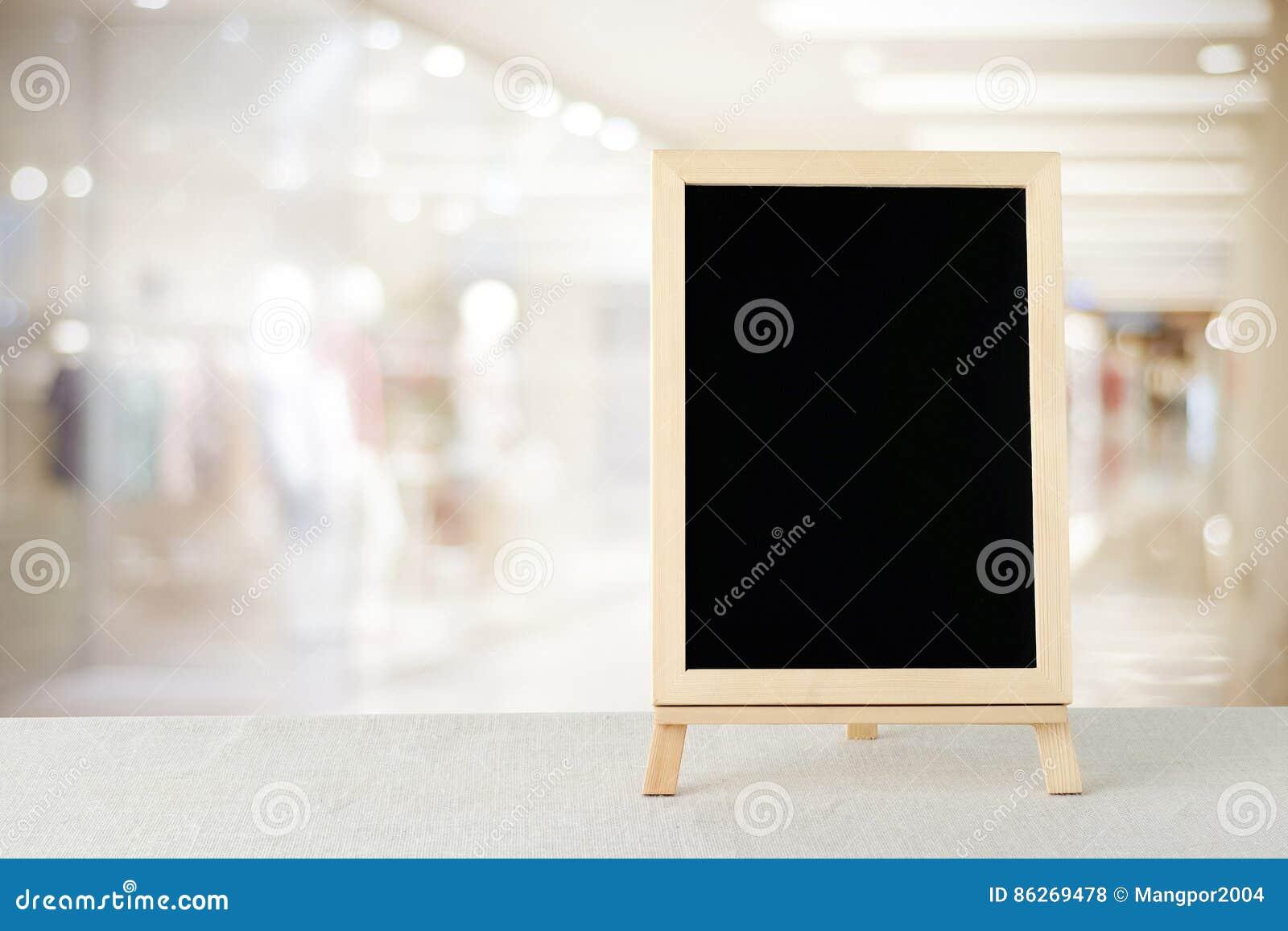 Pizarra en blanco que se coloca en mantel del saco sobre tienda de la falta  de definición con el fondo del bokeh 7b674ccae43c