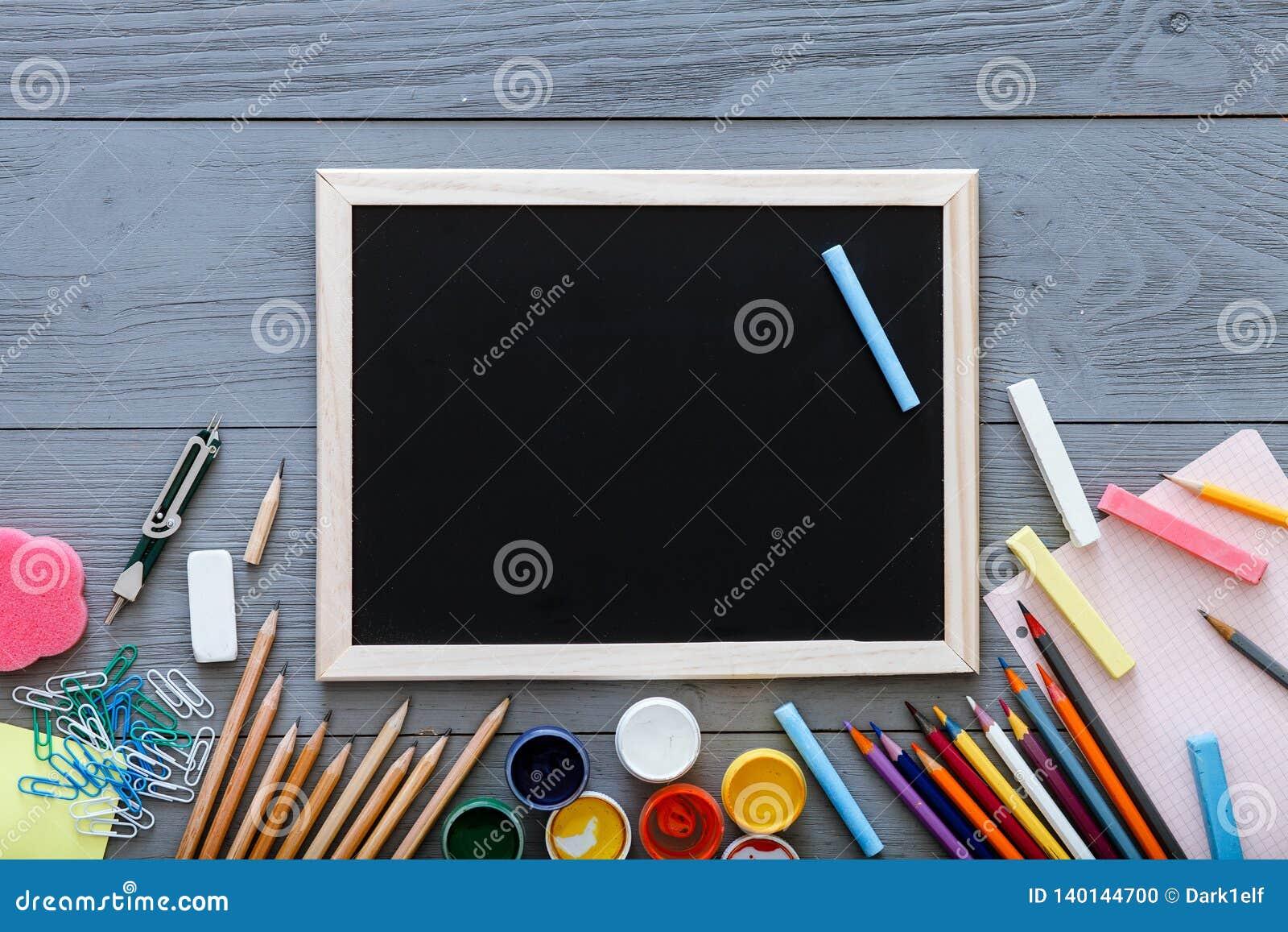 Pizarra en el escritorio oscuro gris con los lápices coloridos, pinturas, otras fuentes de escuela para el schoolwork, de nuevo a