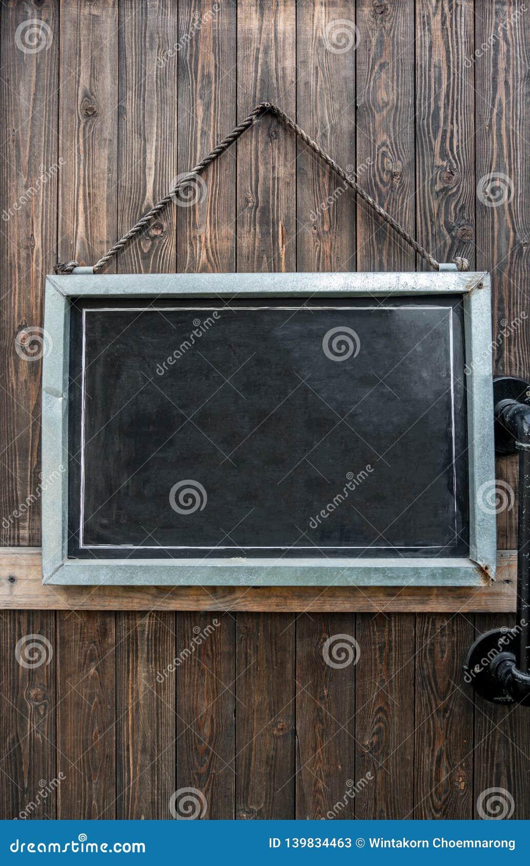 Pizarra rústica en blanco que cuelga en puerta de madera