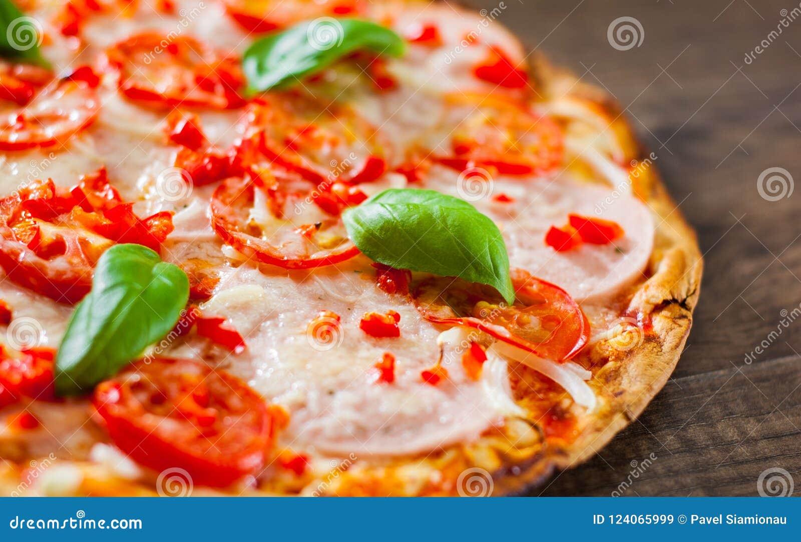 Pizza avec du fromage de mozzarella, le jambon, les tomates, le poivre, les épices et le Basil frais Pizza italienne sur en bois