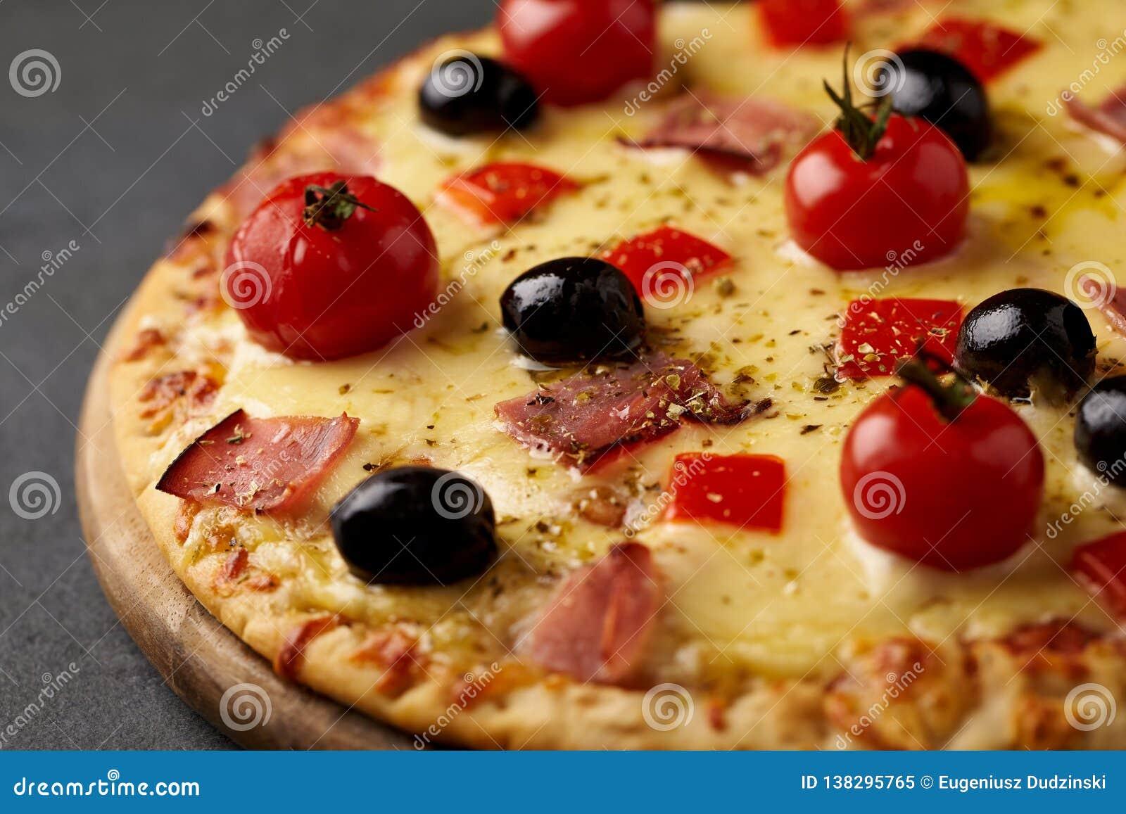 Pizza avec du jambon, le fromage de mozzarella, les tomates-cerises, le poivron rouge, les olives noires et l origan La maison a