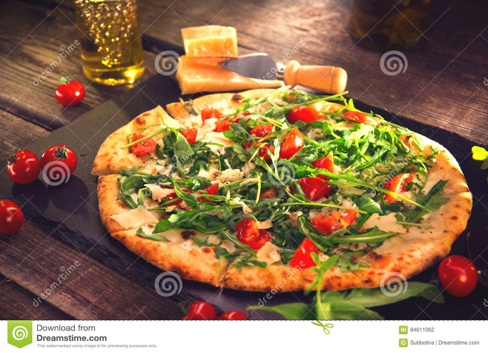 Pizza Caprese with arugula, cheese, yoghurt and cherry tomatoes