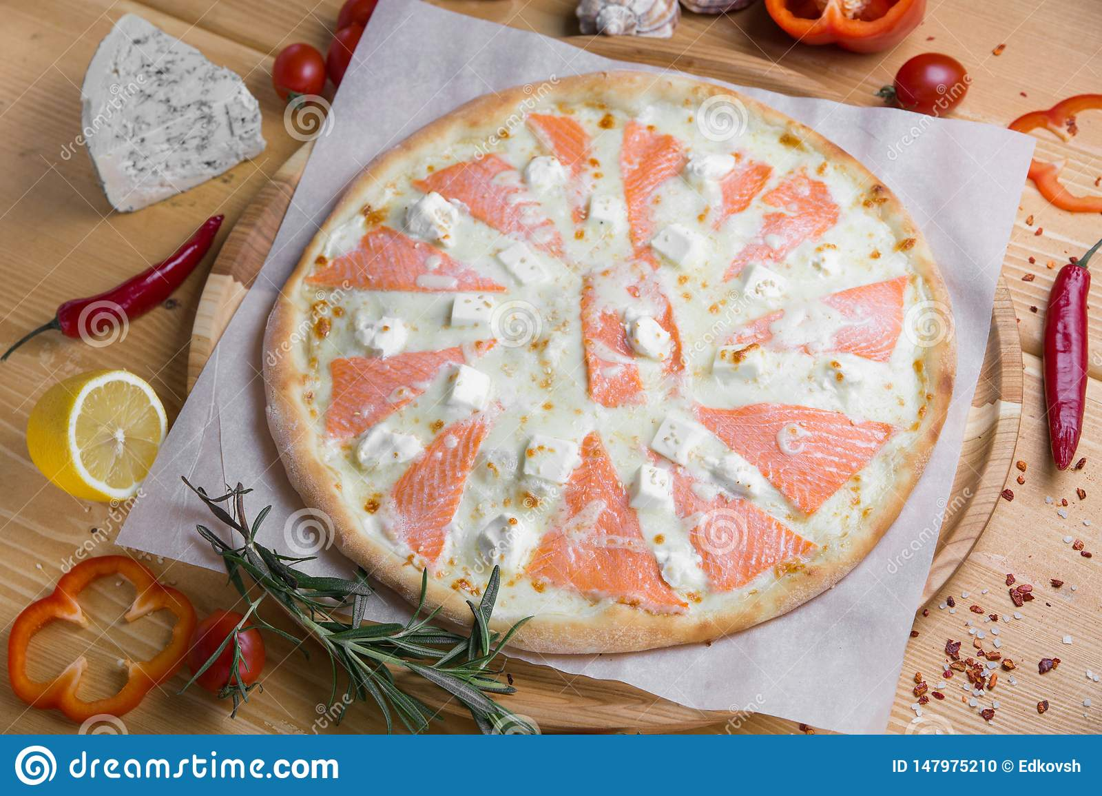 Pizza caseiro com alimento de mar e os peixes vermelhos em um fundo de madeira com frutas e legumes com especiarias